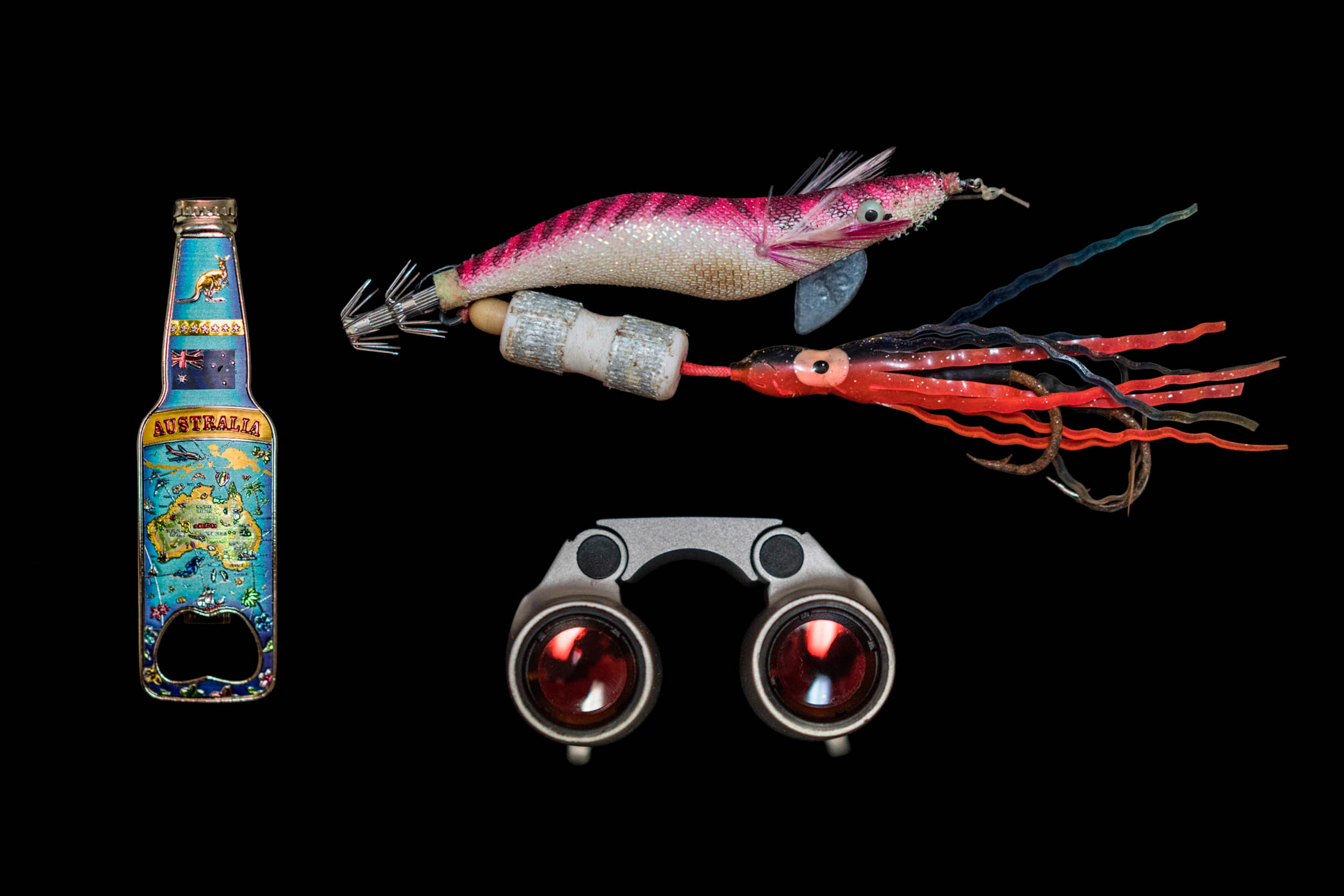 A bottle opener, a fishing lure, and a pair of binoculars. Seafarers entertain themselves fishing or simply