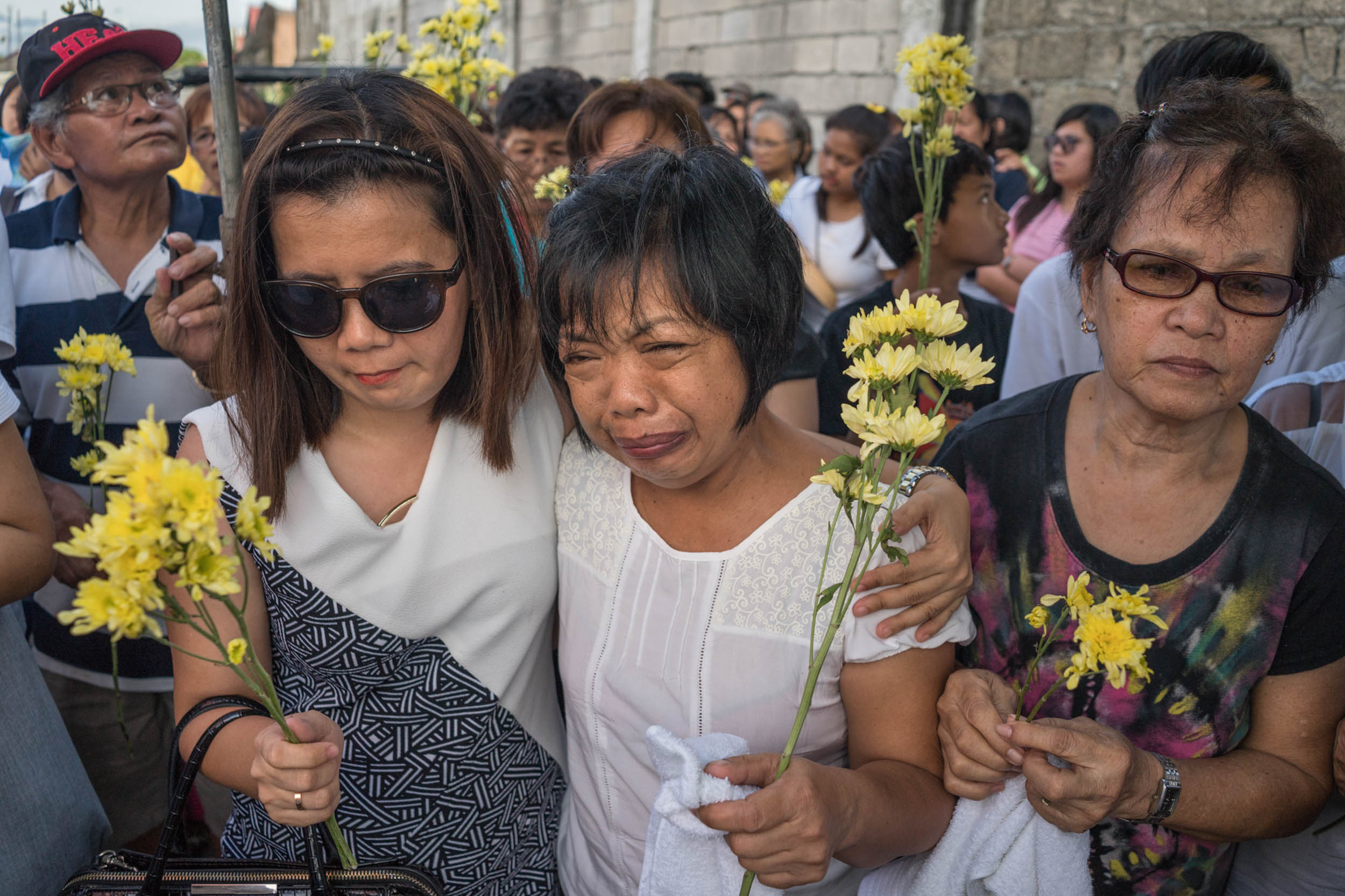 Some of the Filipinos who go abroad with dreams come home in caskets. The mother (center) of Jessica Catiis weeps at her funeral. Catiis was a domestic worker in Saudi Arabia who allegedly died by suicide. Her body was sent back seven months later