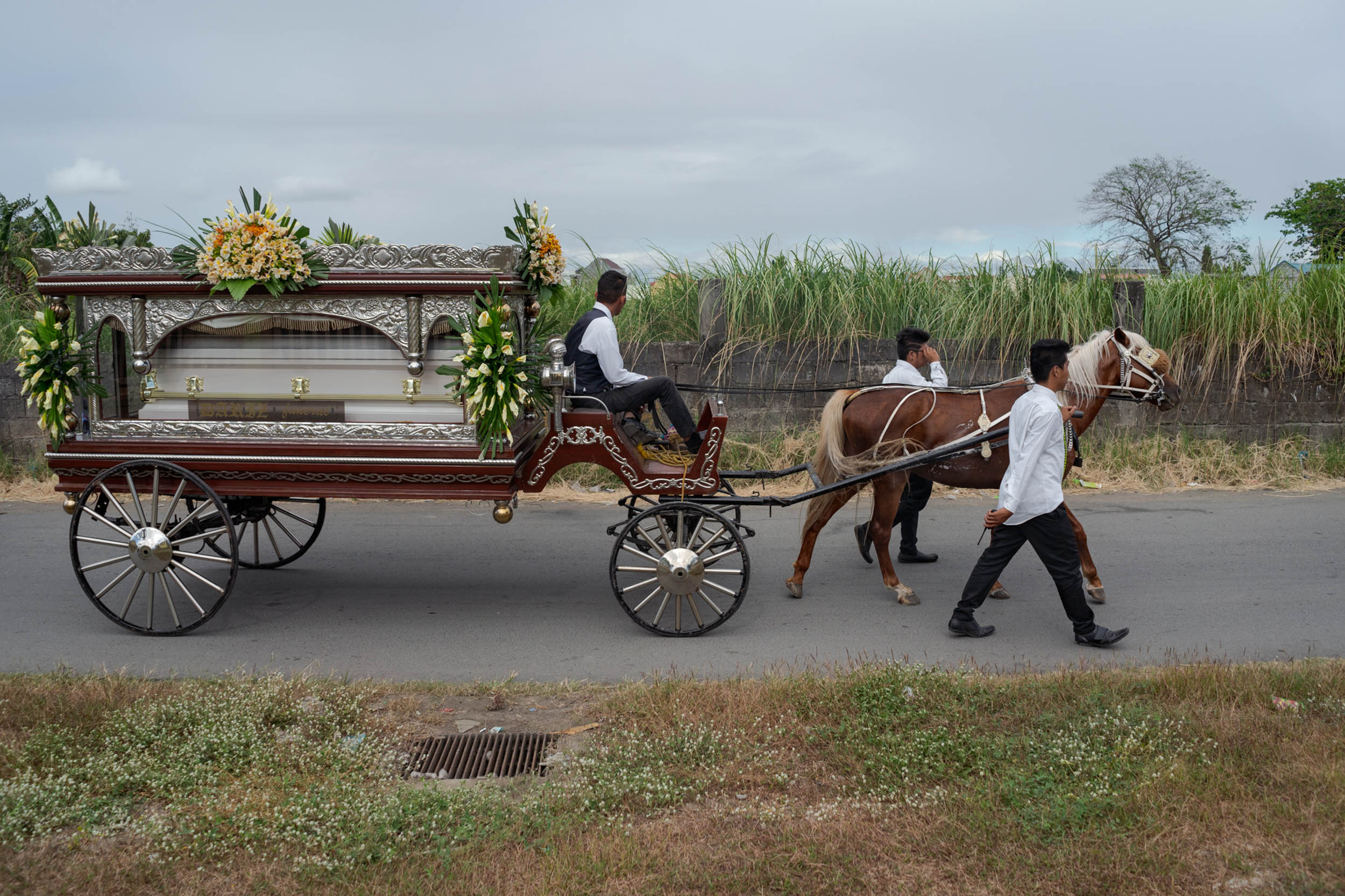 The remains of Jessica Catiis are taken to the cemetery in a horse-drawn carriage. Her mother, Evelyn, and