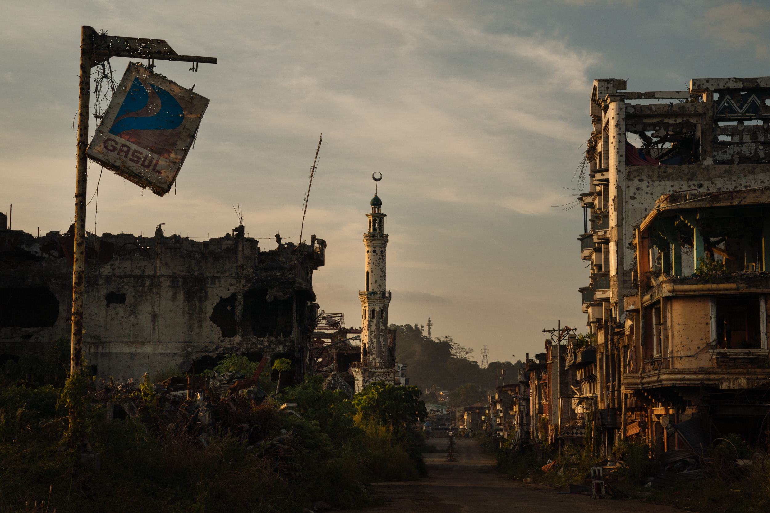 "The ruins of Marawi City are seen at sunset. It has been more than a year since the Philippine military declared the Muslim-majority city of Marawi ""liberated"" from ISIS-linked militants, but the city remains a ghost town, and locals are becoming more and more frustrated with the lack of government support. Marawi's youth, among the most vulnerable, are now faced with forming their identity amidst trauma and conflict."