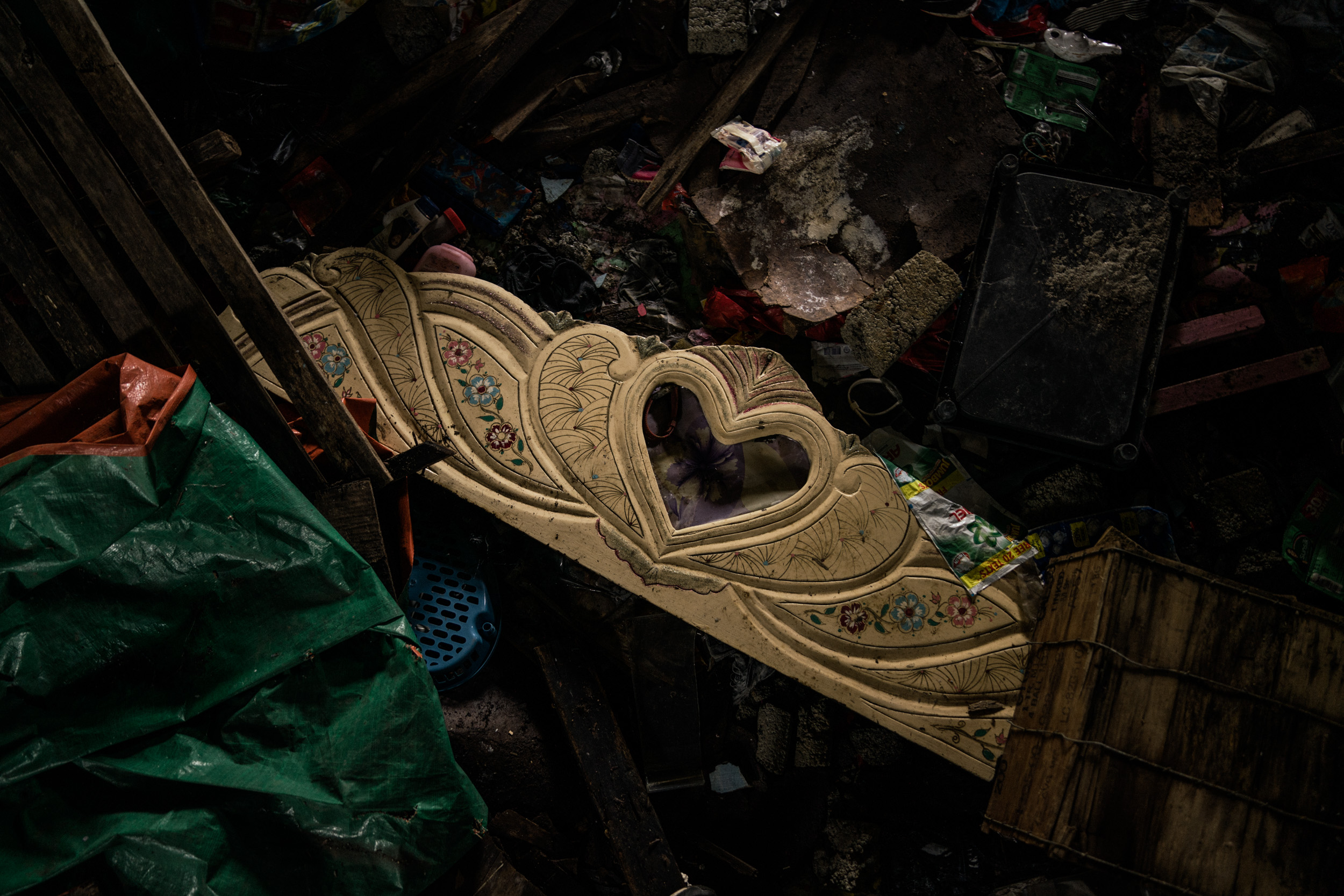 "MARAWI, PHILIPPINES. JANUARY 10. A headboard of a bed is seen in the rubble of the main battle area of the Marawi siege. It has been more than a year since the Philippine military declared the Muslim-majority city of Marawi ""liberated"" from ISIS-linked militants. But the ravaged city is still waiting for billions in promised infrastructure and aid to arrive. Over a hundred thousand people remain displaced, and analysts say that militants are returning to the area, preying on growing frustration with the government in maintaining stability. (Hannah Reyes Morales for The Washington Post)"
