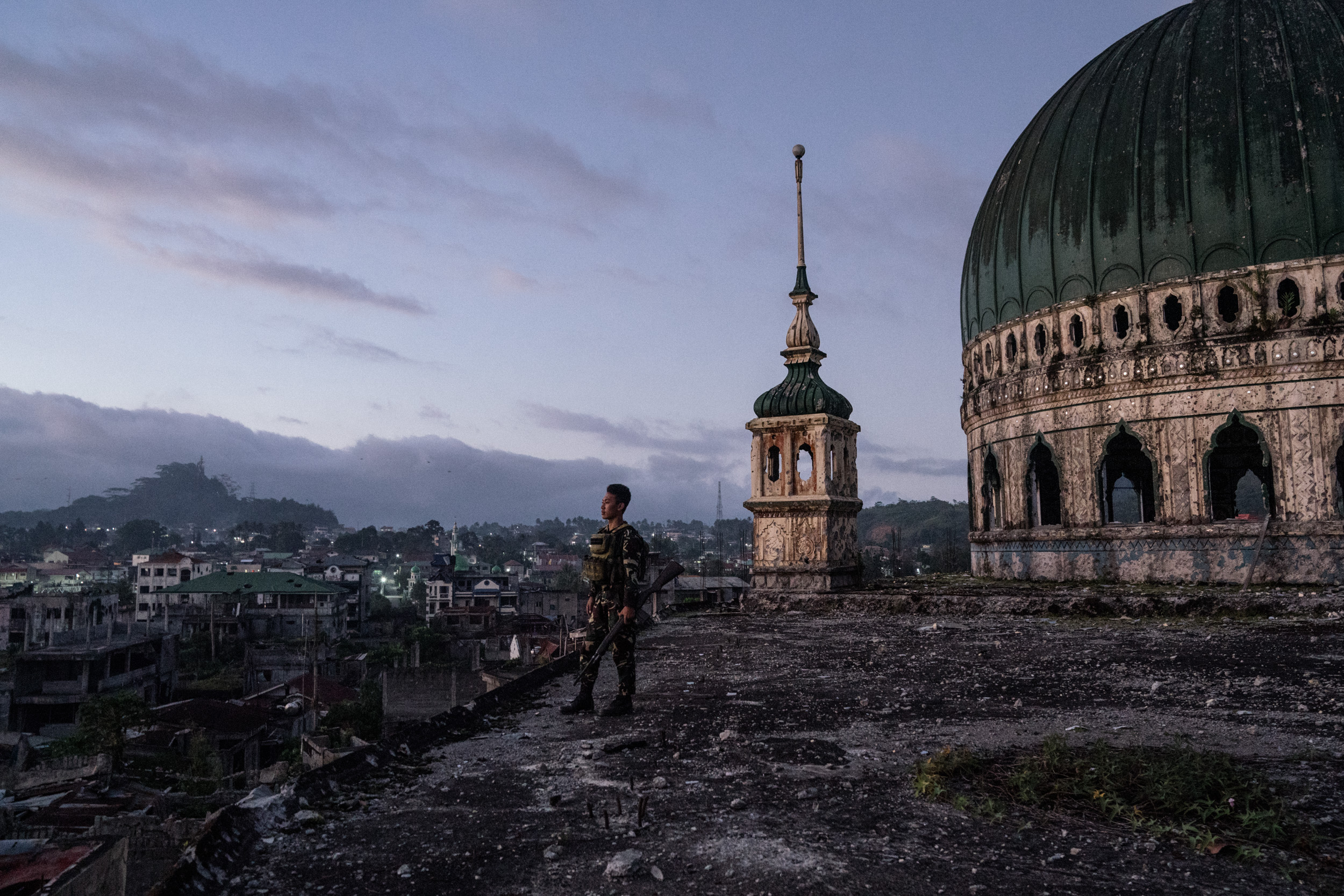 "MARAWI, PHILIPPINES. JANUARY 8. A soldier is seen in the Grand Mosque, which was destroyed during the Marawi siege. The masjid is still damaged more than a year since the Philippine military declared the Muslim-majority city of Marawi ""liberated"" from ISIS-linked militants. But the ravaged city is still waiting for billions in promised infrastructure and aid to arrive. Over a hundred thousand people remain displaced, and analysts say that militants are returning to the area, preying on growing frustration with the government in maintaining stability. (Hannah Reyes Morales for The Washington Post)"