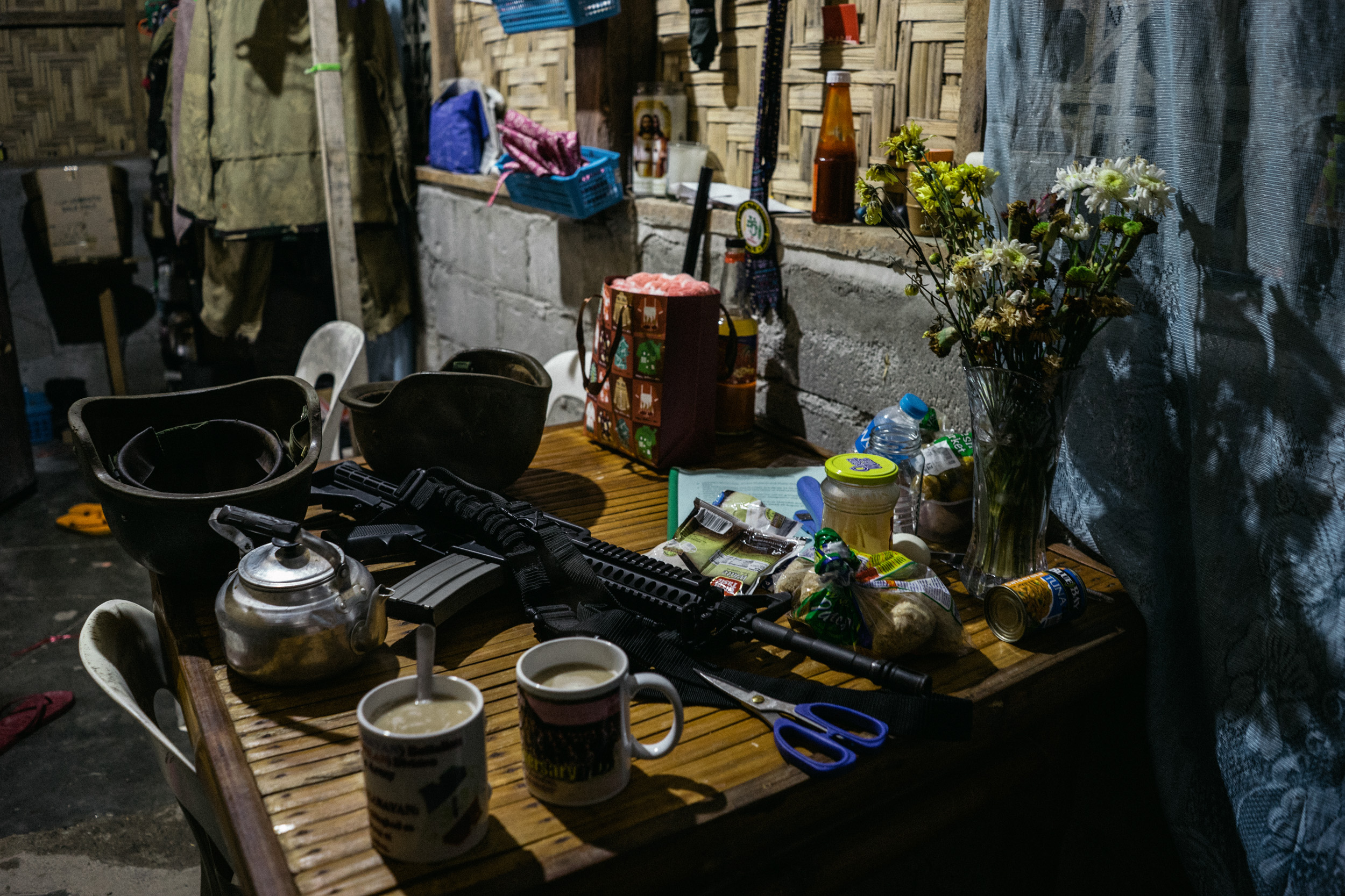 A gun is seen on the table of an Armed Forces of the Philippines (AFP) battalion's ladies' barracks, beside flowers from an officer's boyfriend.
