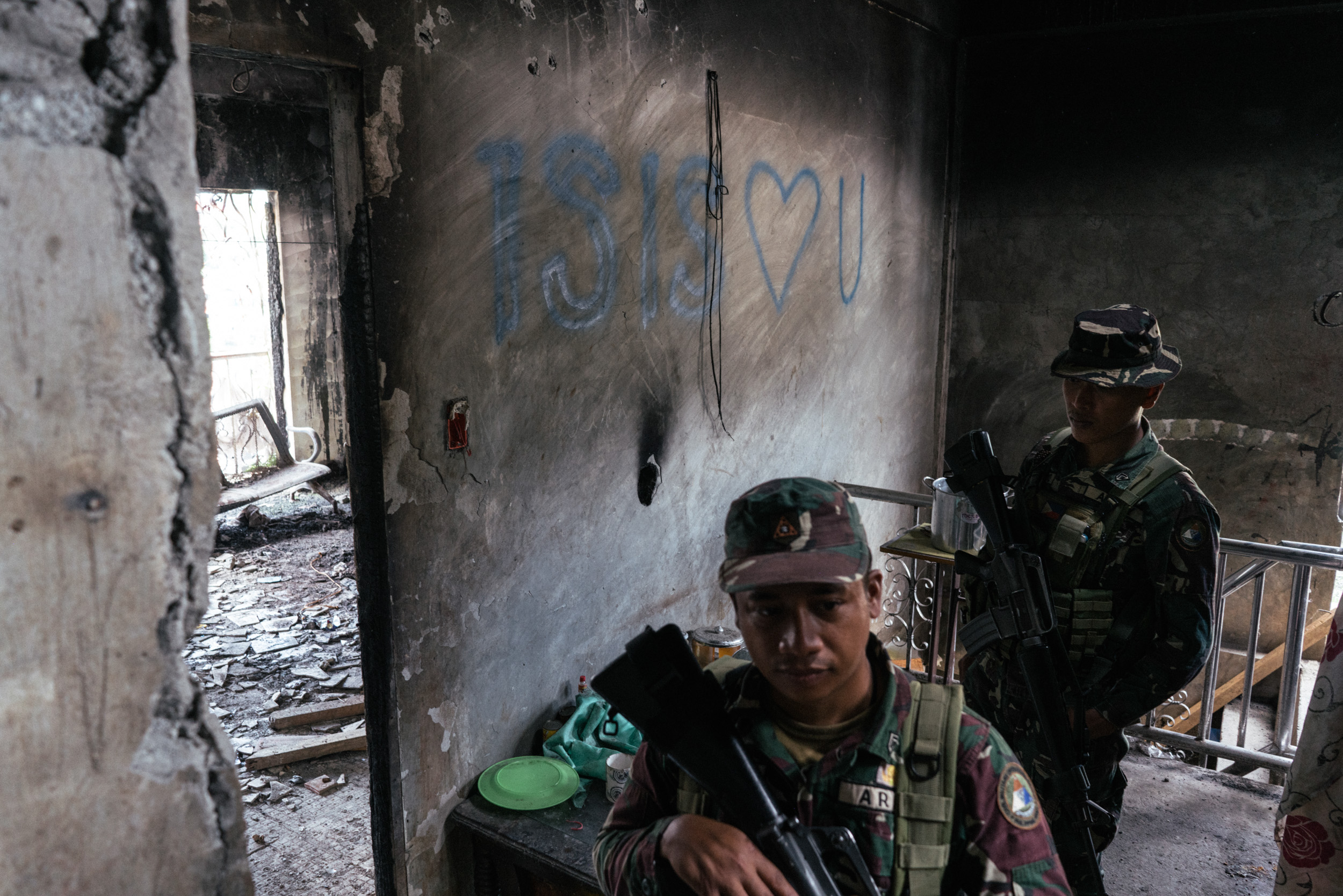MARAWI CITY, PHILIPPINES. NOVEMBER 15. Filipino soldiers are seen by a wall with the graffiti 'ISIS  ? U' in Marawi, Philippines on November 15, 2017. Marawi  City is in ruins after Islamic State (IS) inspired militants laid siege to the city in a battle that lasted for five months, displacing hundreds of thousands of people. (Photo by Hannah Reyes Morales for The Washington Post)