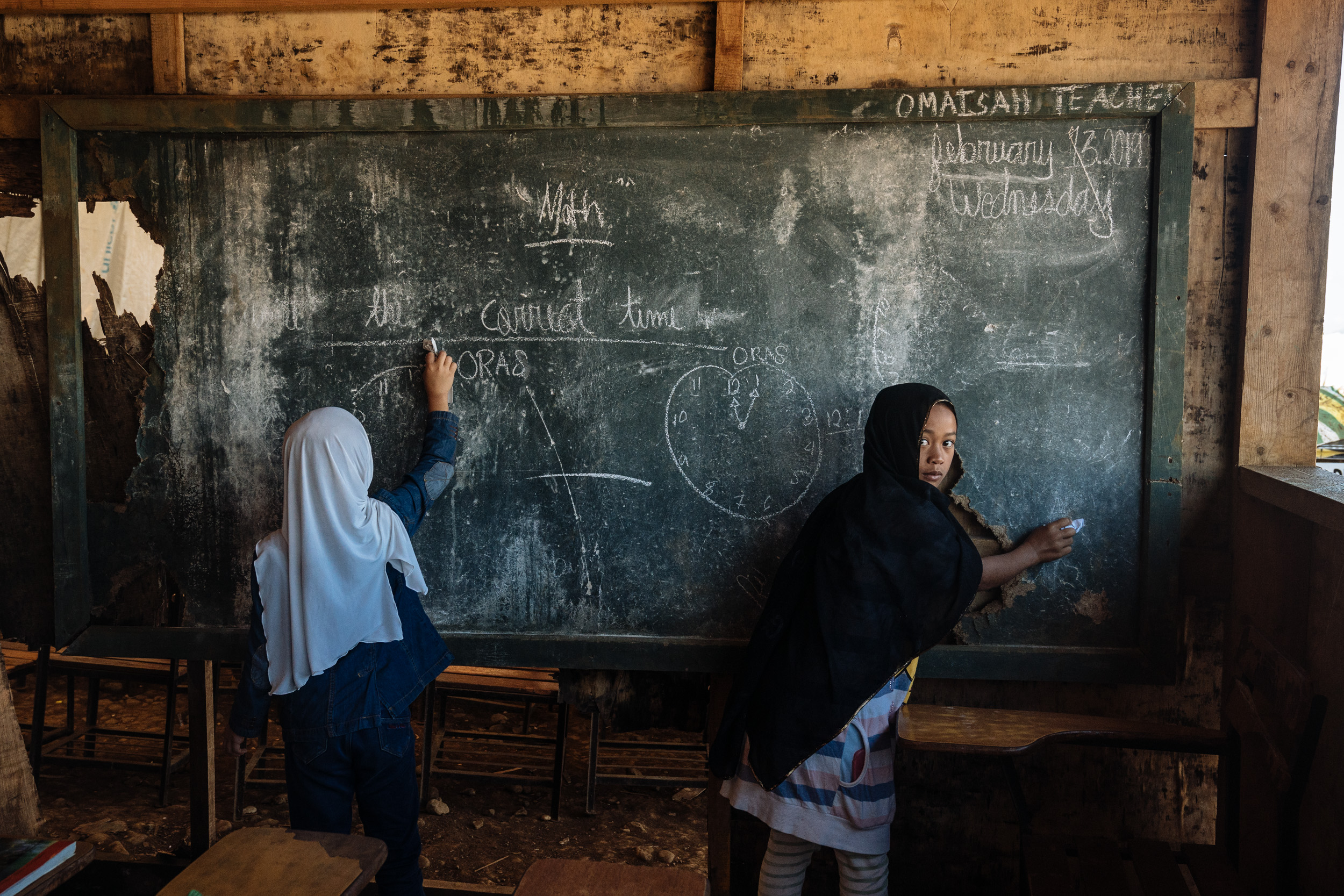 "Young girls are seen erasing the blackboard of their makeshift classroom in a camp for internally displaced youth in Marawi City. It has been more than a year since the Philippine military declared the Muslim-majority city of Marawi ""liberated"" from ISIS-linked militants, but the city remains a ghost town, and locals are becoming more and more frustrated with the lack of government support. Marawi's youth, among the most vulnerable, are now faced with forming their identity amidst trauma and conflict."