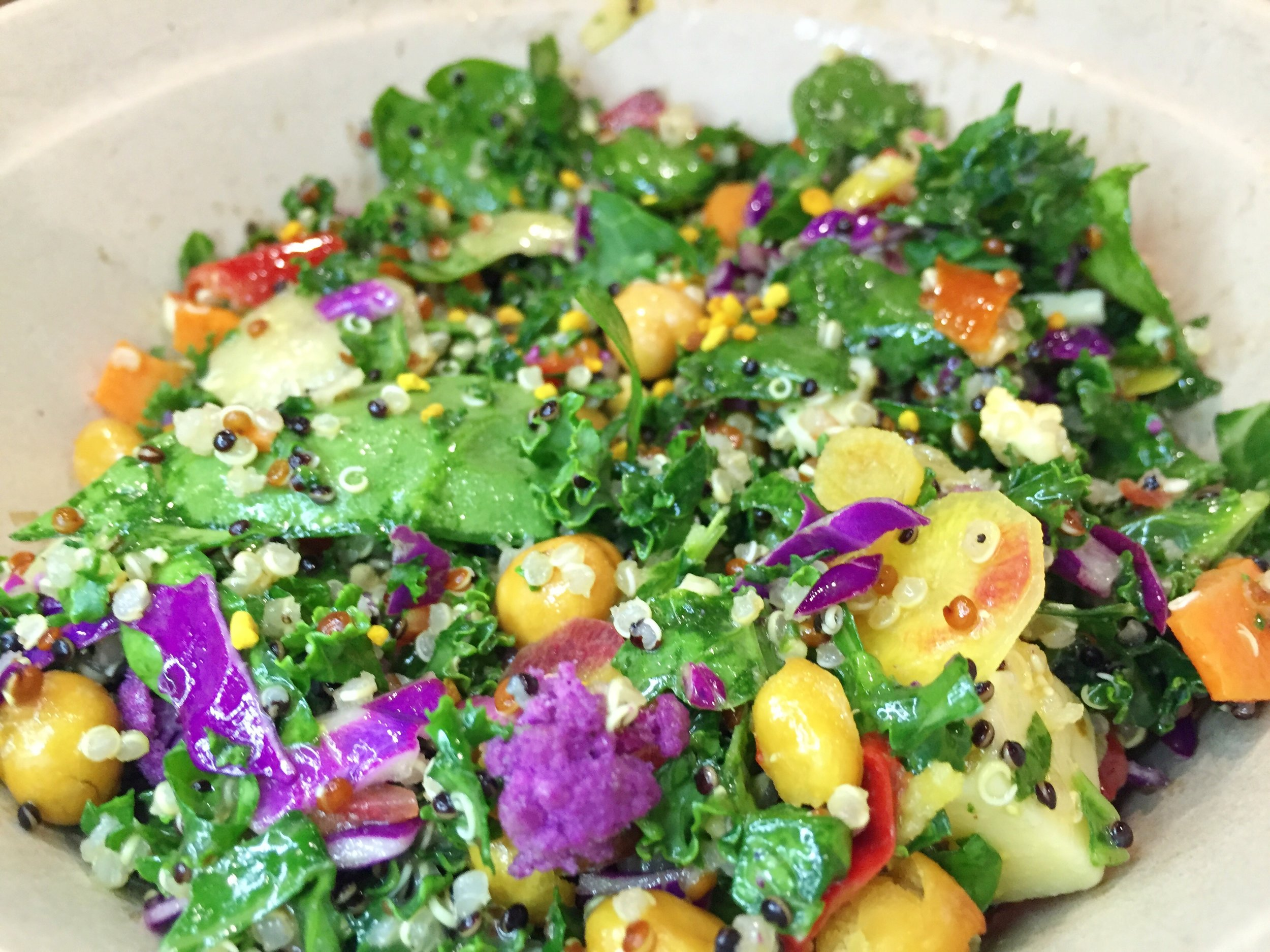 Beekeeper's Quinoa Bowl | Tri-colored quinoa, aged Tillamook cheddar, roasted chickpeas, Mama Lil's spicy peppers, rainbow cauliflower, kale, broccoleaf, purple cabbage. Tossed in Wildflower Honey Dijon dressing and topped with bee pollen.