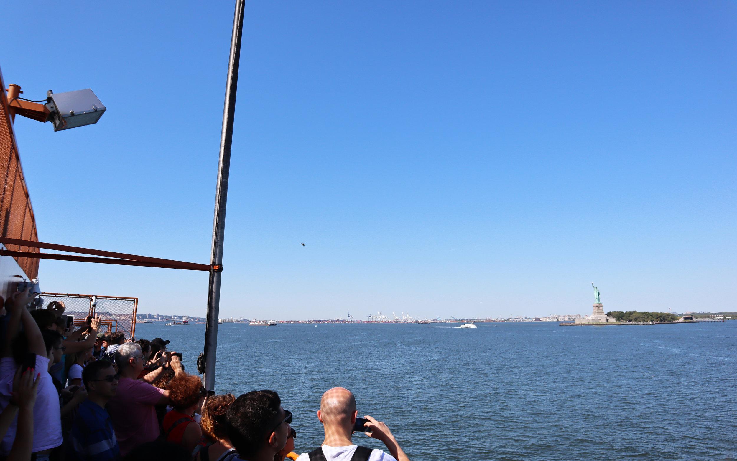 Туристы на борту парома и Статуя Свободы