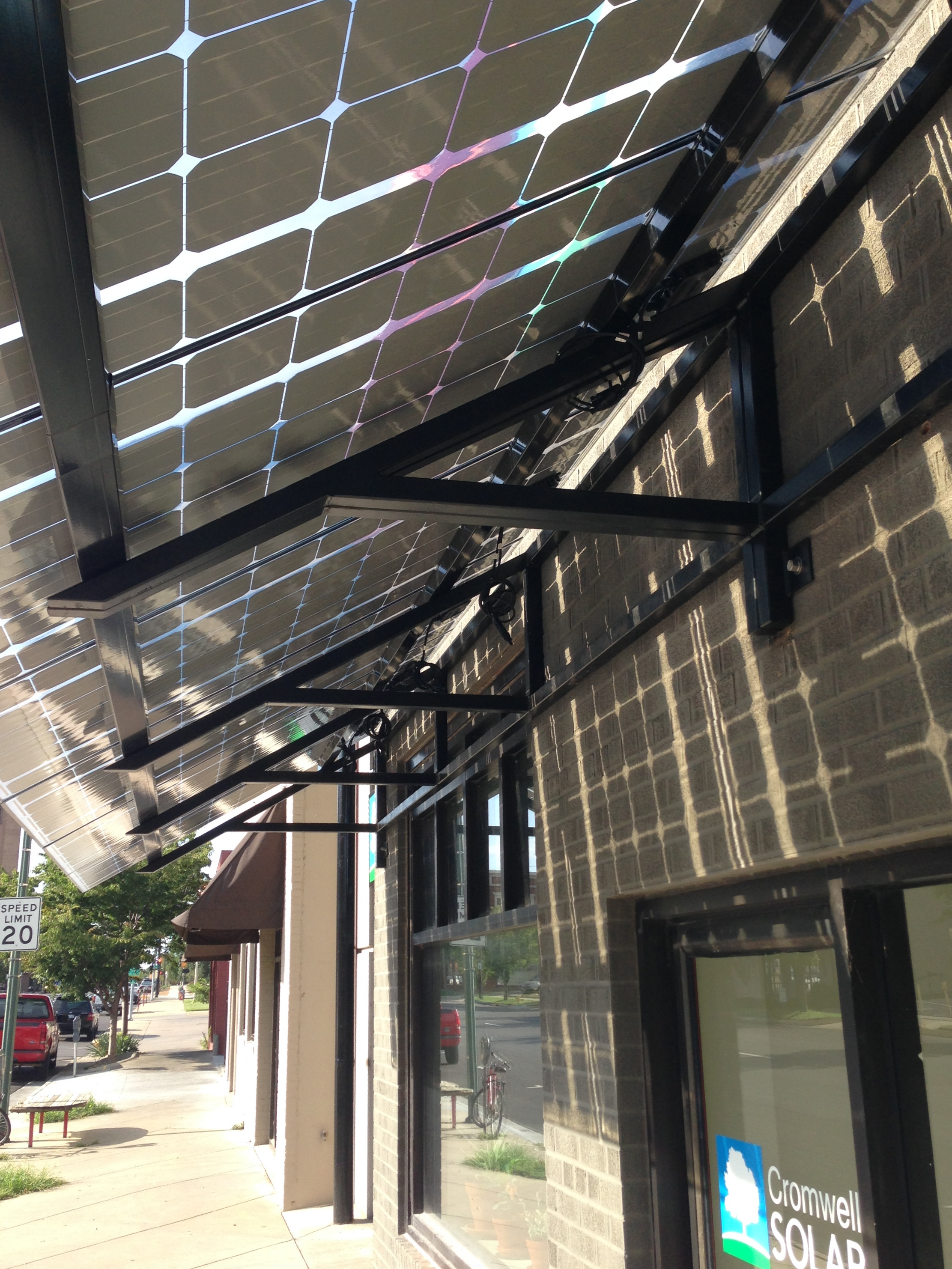 Bi-facial, frameless solar panels are used as an architectural feature on a custom solar awning for our office.