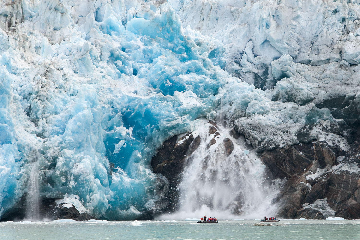 At the mouth of a glacier within Alaska's Inside Passage, travelers in Zodiac boats navigate water around icebergs and witness calving.