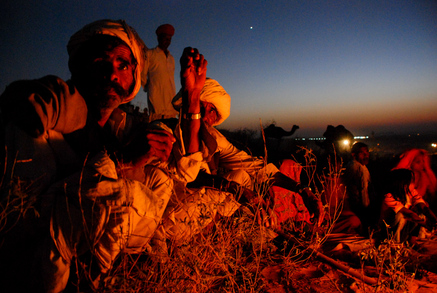 At The Pushkar Camel Fair in India, a family gathers around a campfire at dusk to stay warm and prepare a meal.