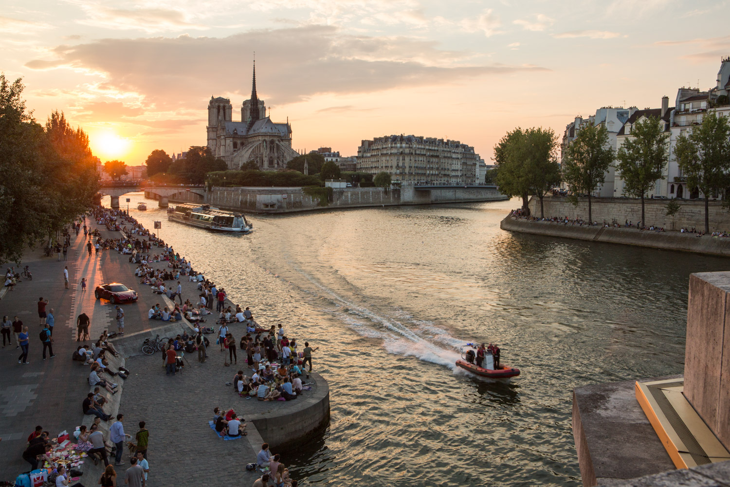 A small speedboat navigates the Seine River in Paris, France. Parisians and tourists line the riverbanks as the sun sets behind the Notre Dame Cathedral.