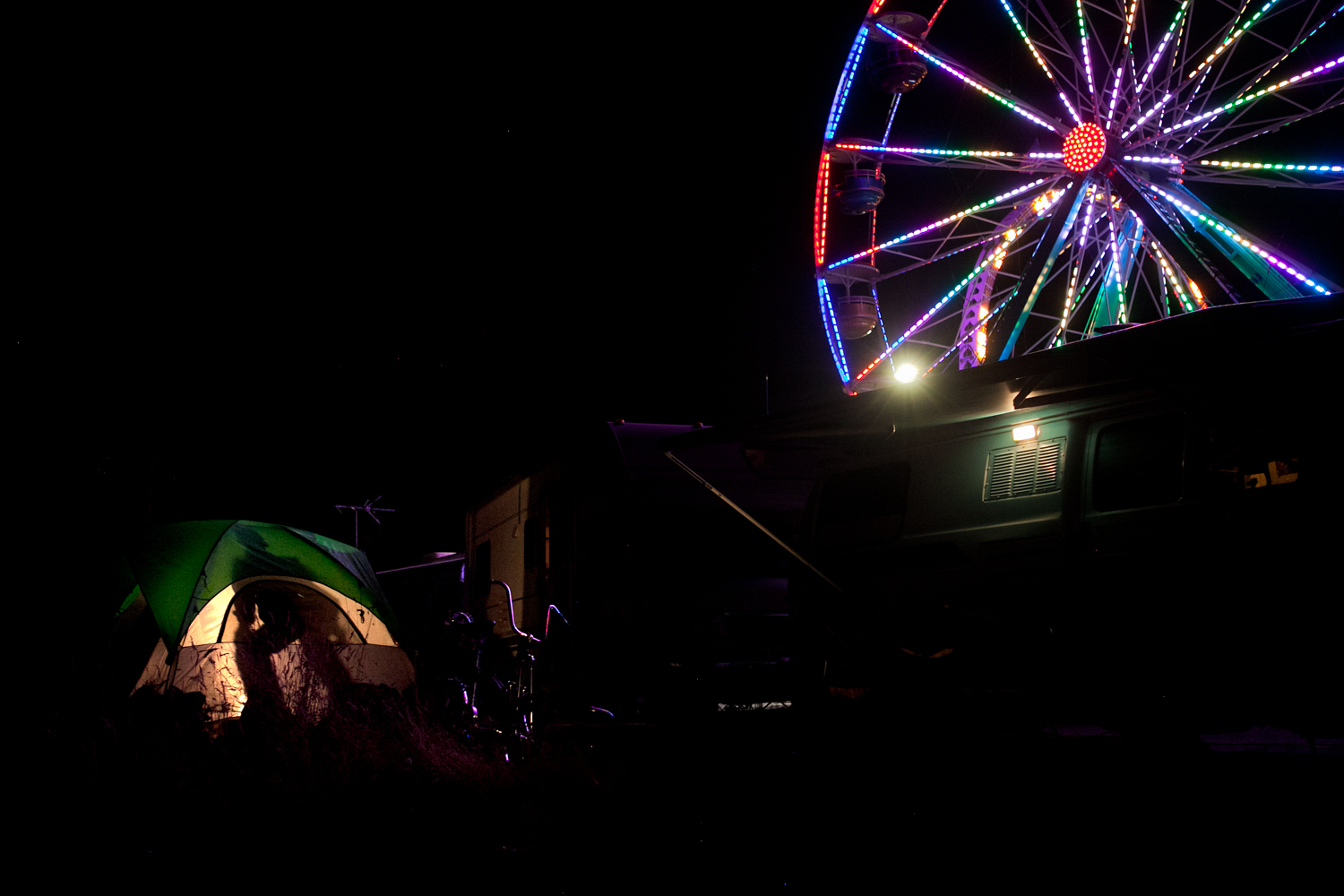 Workers setup camp and live in close proximity to the carnival grounds. At night, a man prepares for bed in his tent while the Ferris Wheel illuminates the surrounding area.