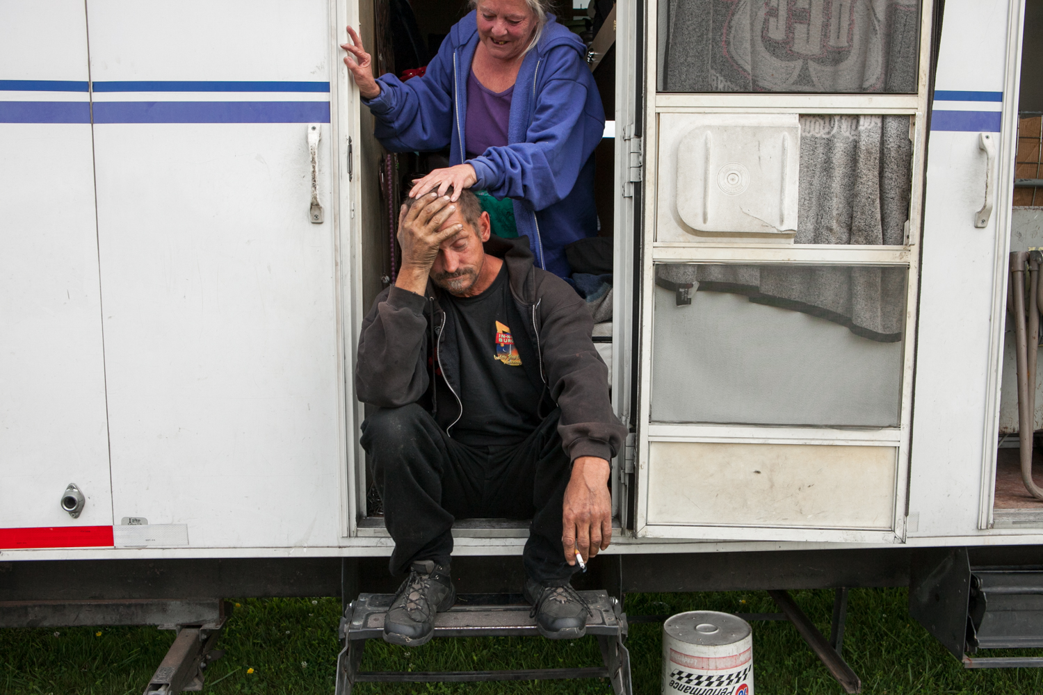 The traveling carnival has a tractor-trailer that is outfitted with 8 individual rooms that act as sleeping quarters / living areas. This married couple shares one of the rooms. As the man sits on his front step and smokes a cigarette, his wife comforts him.
