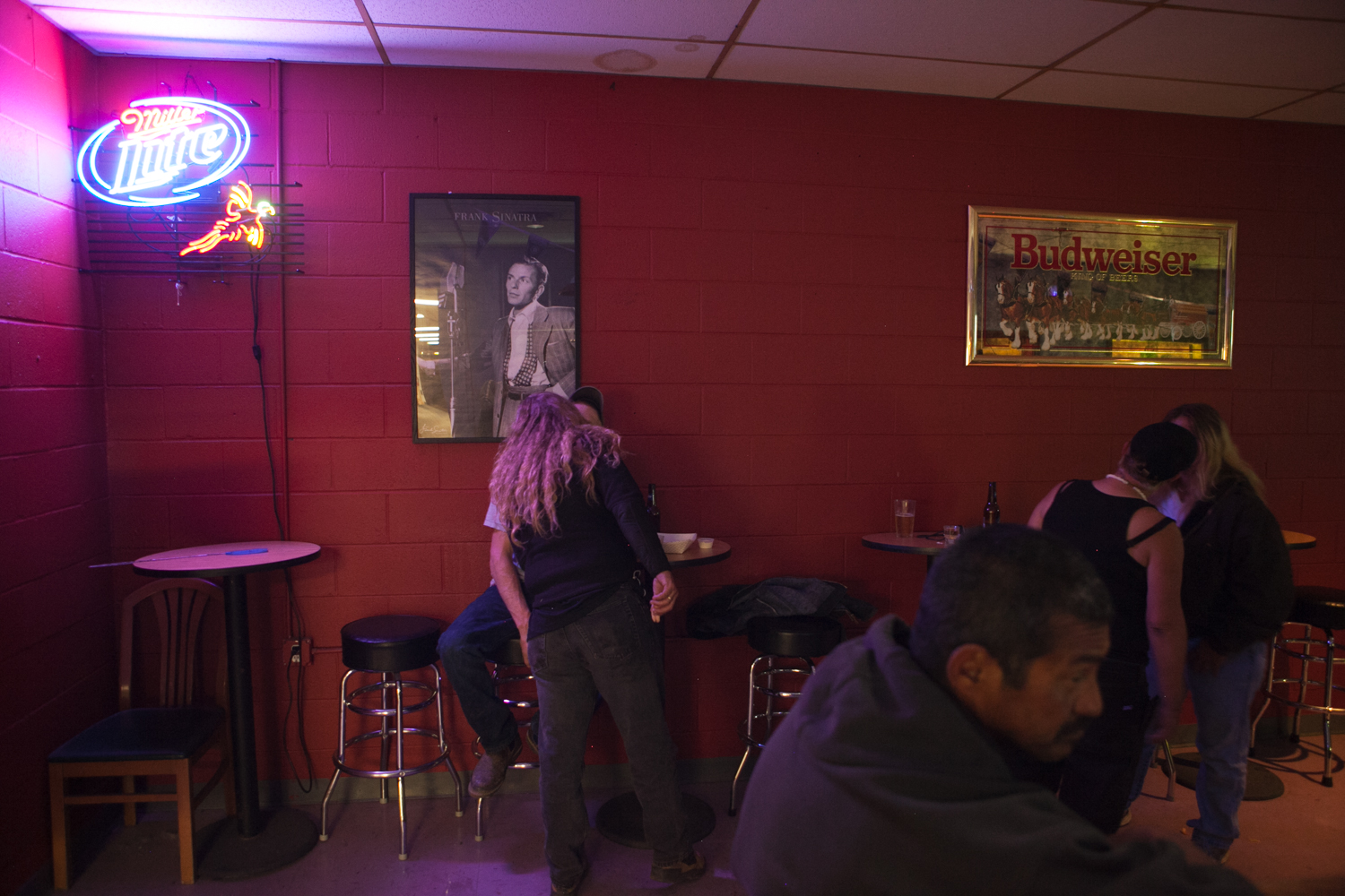 Five carnival workers (one man in the foreground, two couples in the background) spend some free time in a local bar. As the man sits at the bar, the two couples each engage in a kiss.