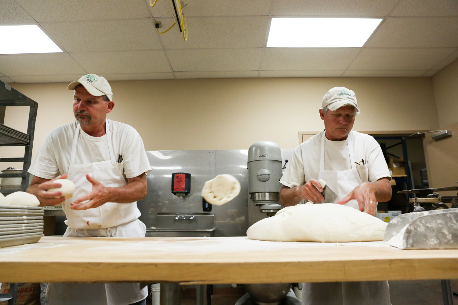 At their family bakery, Paul (right) tosses a piece of dough (used for donuts) to his brother Joe. Each night they prepare about 300 pounds of dough for their signature donuts, in addition to pastries, breads, cakes and others goods.