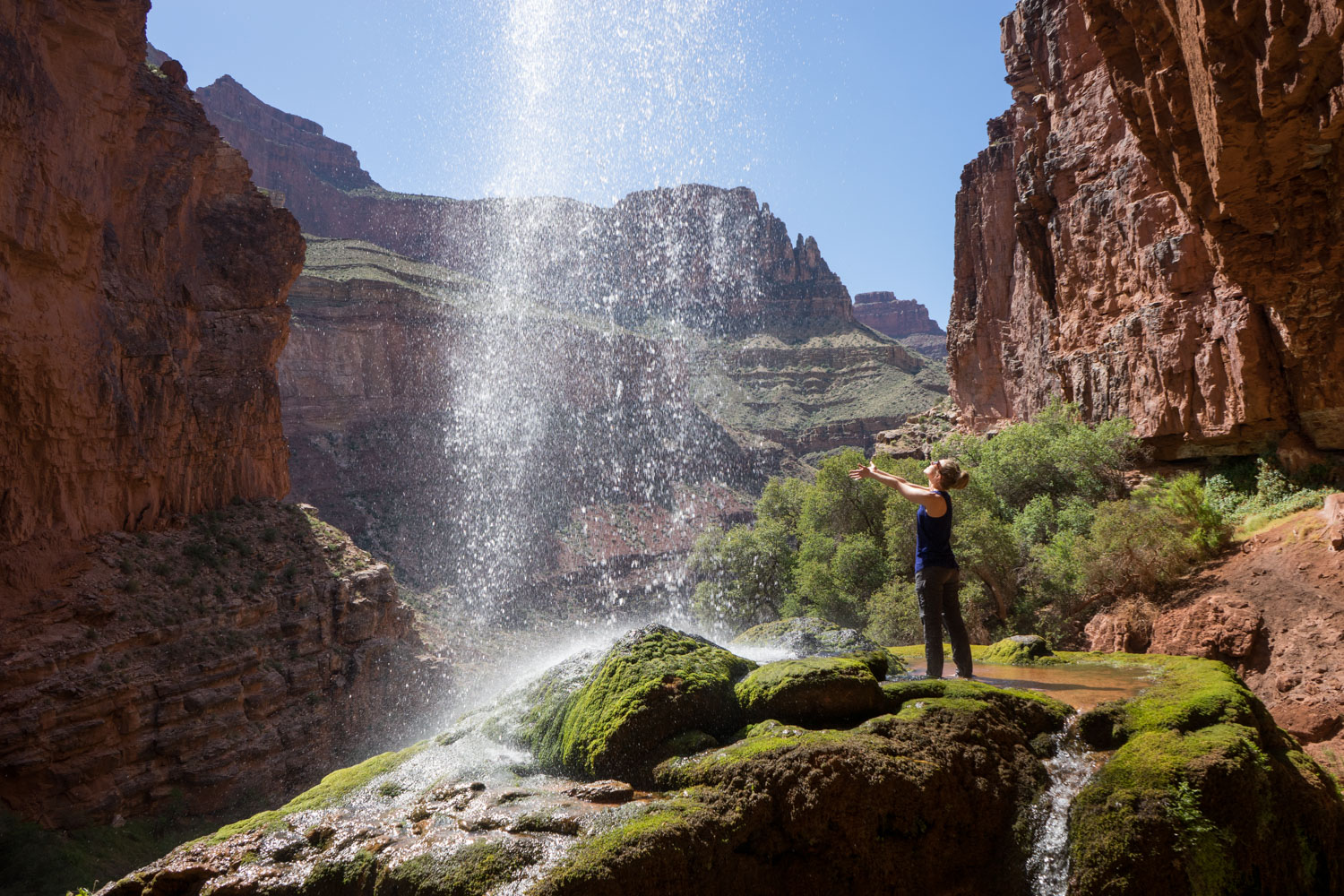 At Ribbon Falls in Arizona's Grand Canyon, a girl stands in a small pool and reaches for the waterfall.