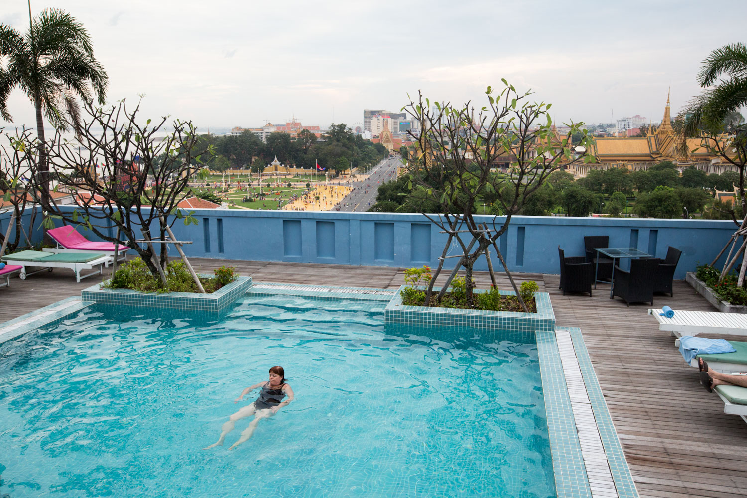 A patron at the Frangipani Royal Palace Hotel in Phnom Pehn, Cambodia, relaxes in a rooftop swimming pool.