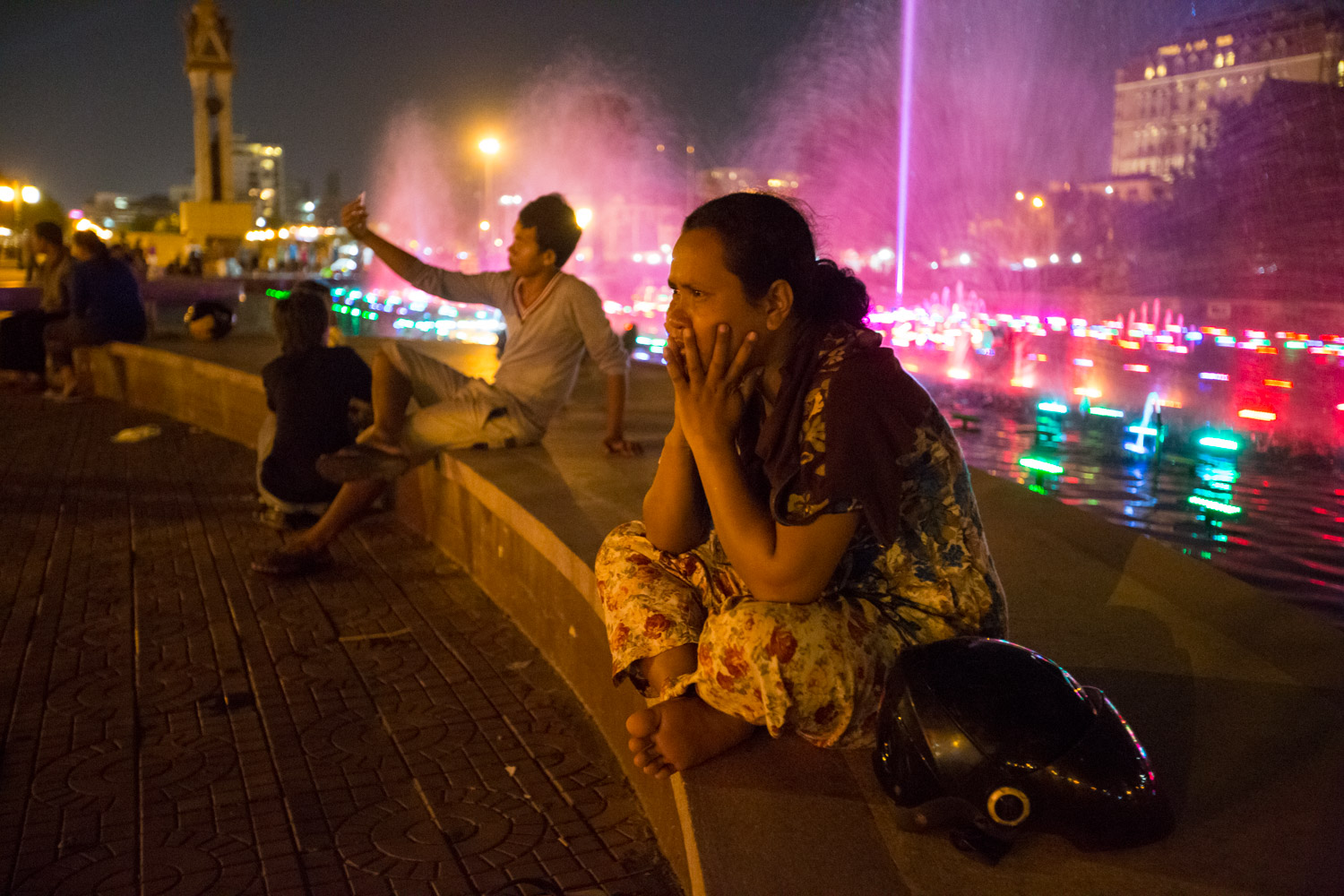 In Phnom Pehn, Cambodia, a local sits near a night-time fountain light show.