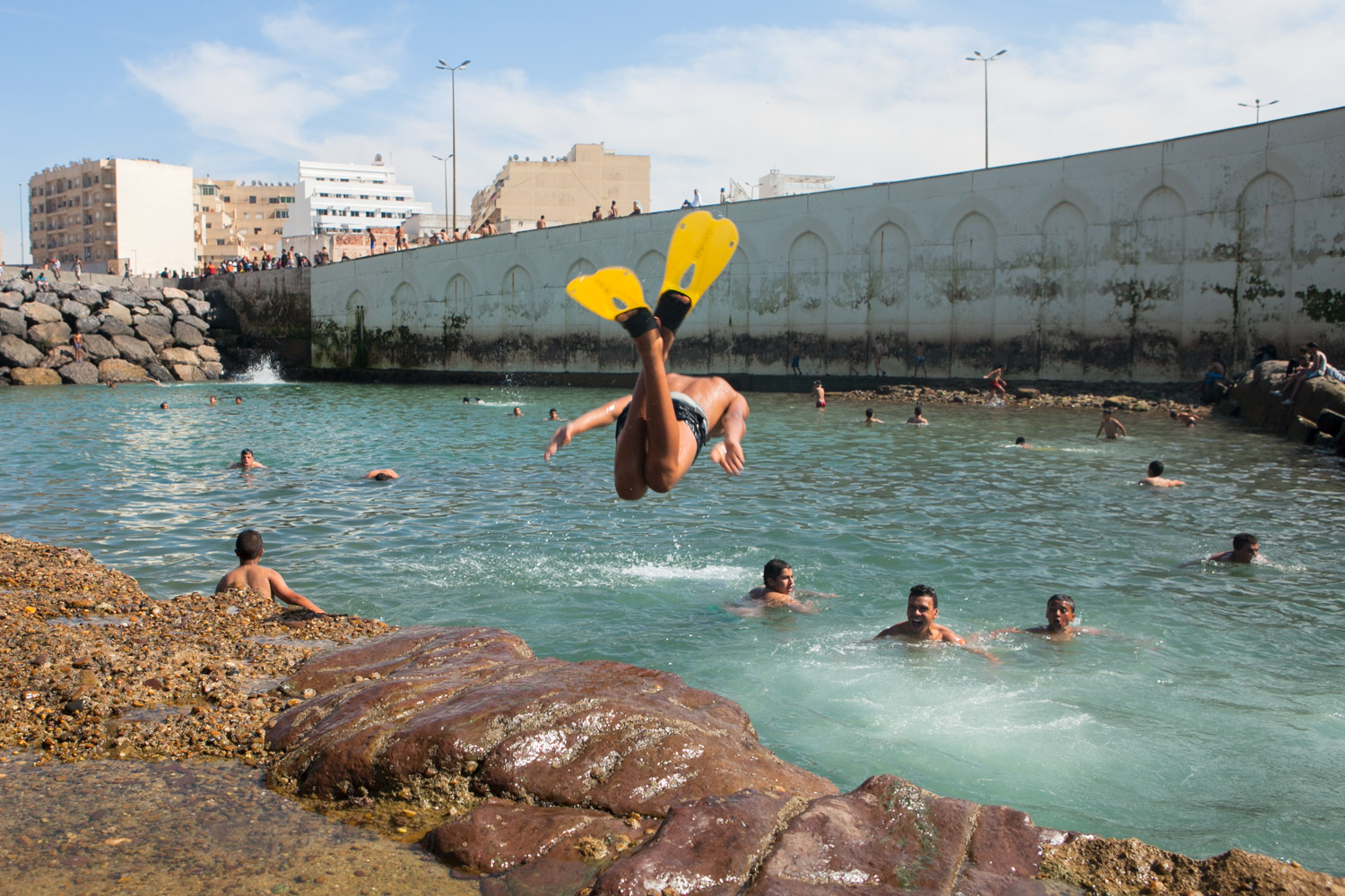 In Casablanca, the conservative metropolis of Morocco, dozens of young boys don swimming suits and buck the trend on a hot summer day. A break-wall, protecting the city from rising seas, combined with rock formations, makes the perfect locale for natural pools as tides rise and recede. The swimming hole grants locals a retreat for relaxation during intense Moroccan summers. One boy, adorned with brightly colored flippers, dives headfirst into the pool.
