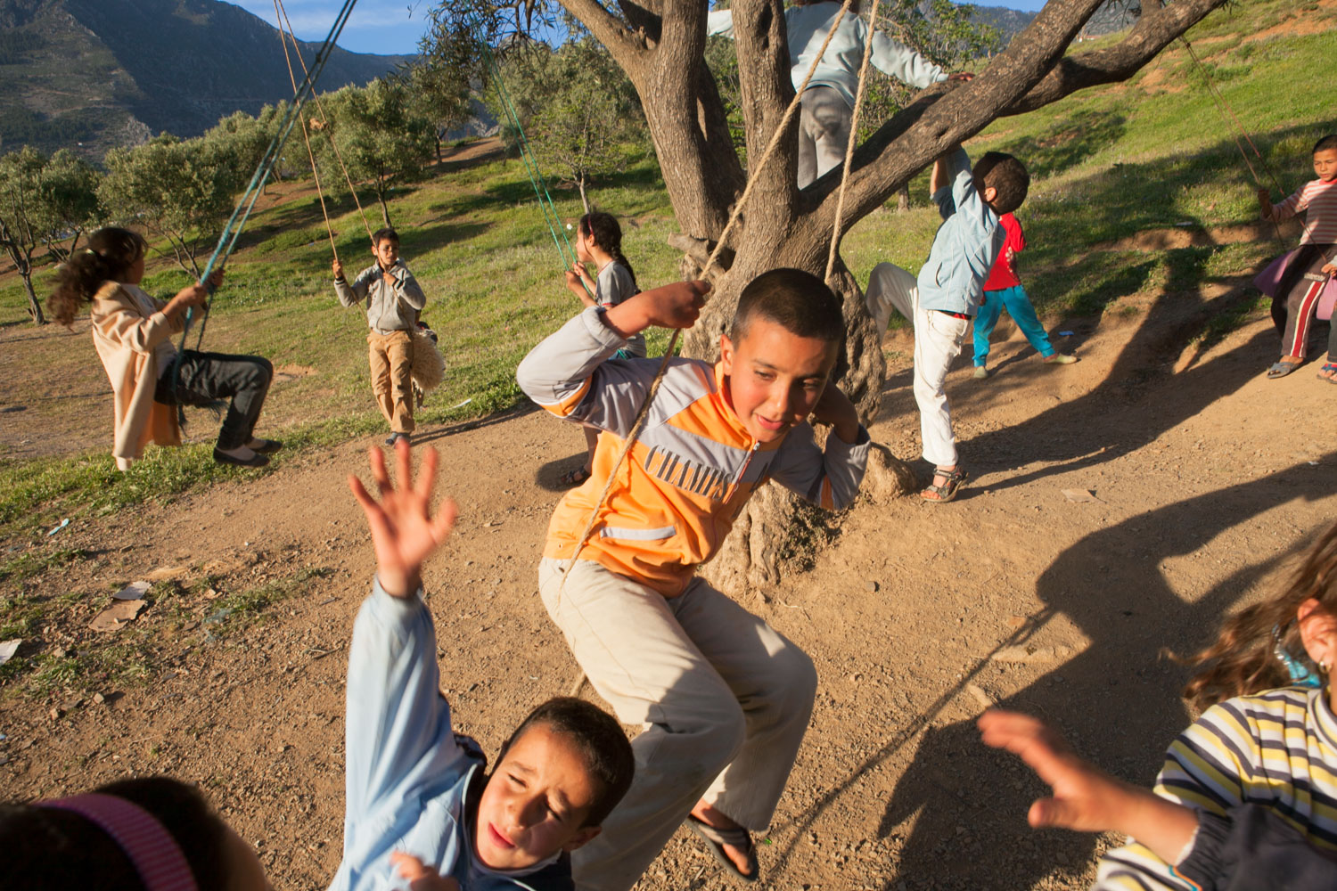 On a hillside outside Chefchaouen, Morocco, children transform a sturdy tree into a central playground that houses multiple swings and offers an area for fun. But with many kids vying for space, one child is struck by another and is flung forward.