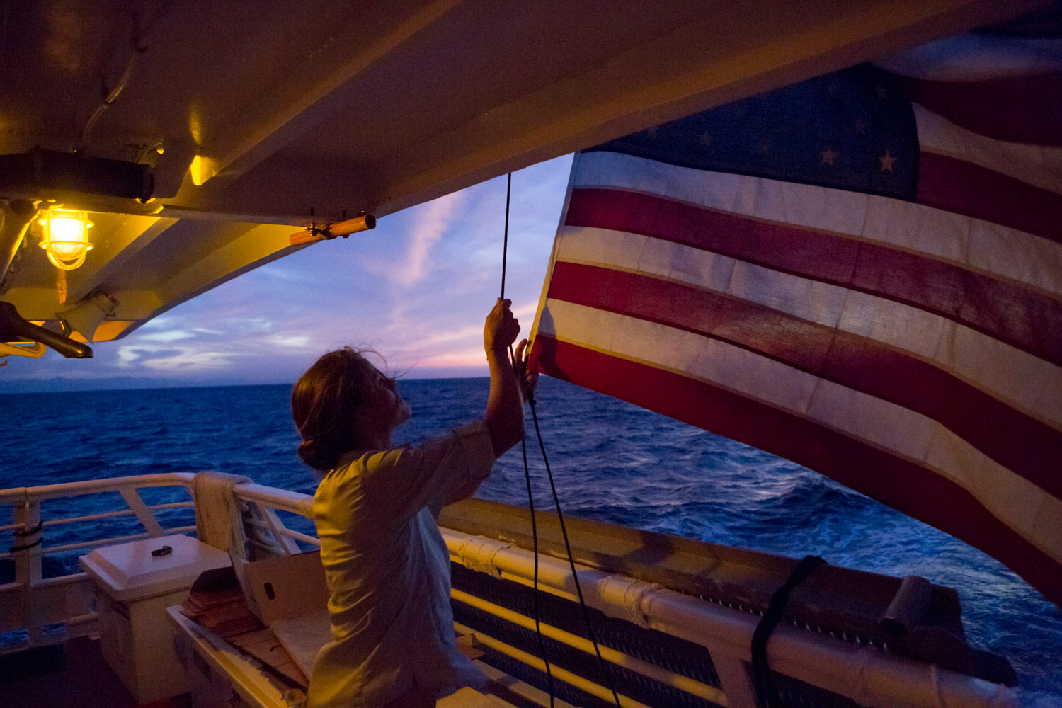 Amidst a colorful morning sky, a deck hand aboard the National Geographic Sea Lion raises the American Flag at dawn.