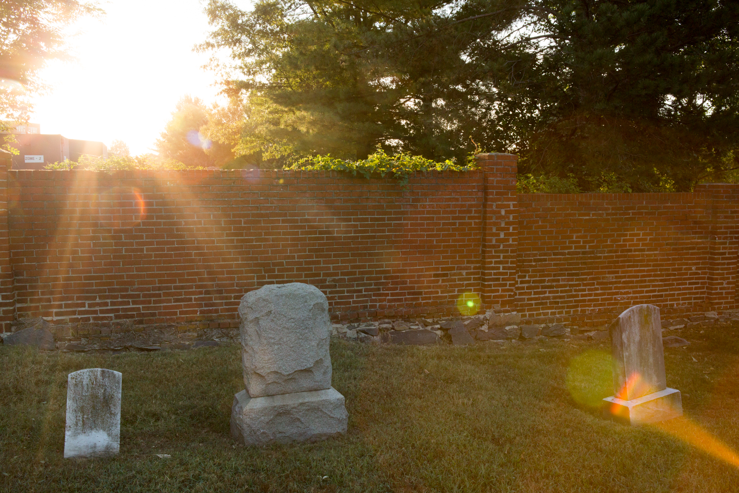 The sun bursts through some trees near several tombstones in the Congressional Cemetery in Washington, D.C.