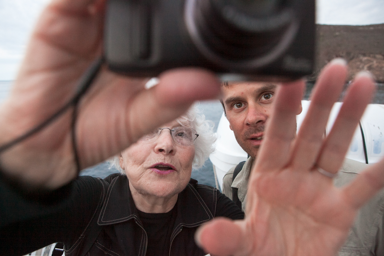 On an expedition vessel in the Galapagos Islands, two passengers view images on the back of a camera.