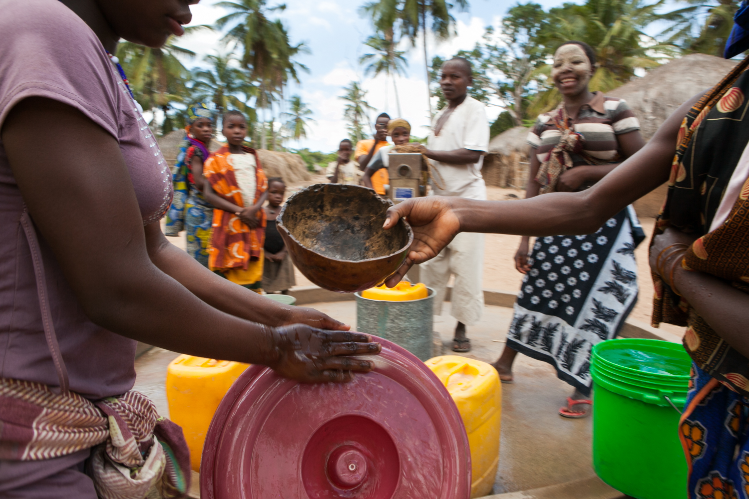 After pump repairs are complete, residents bring their colorful buckets and collect water. They oftentimes utilize a coconut shell for distributing water between buckets and washing their hands.