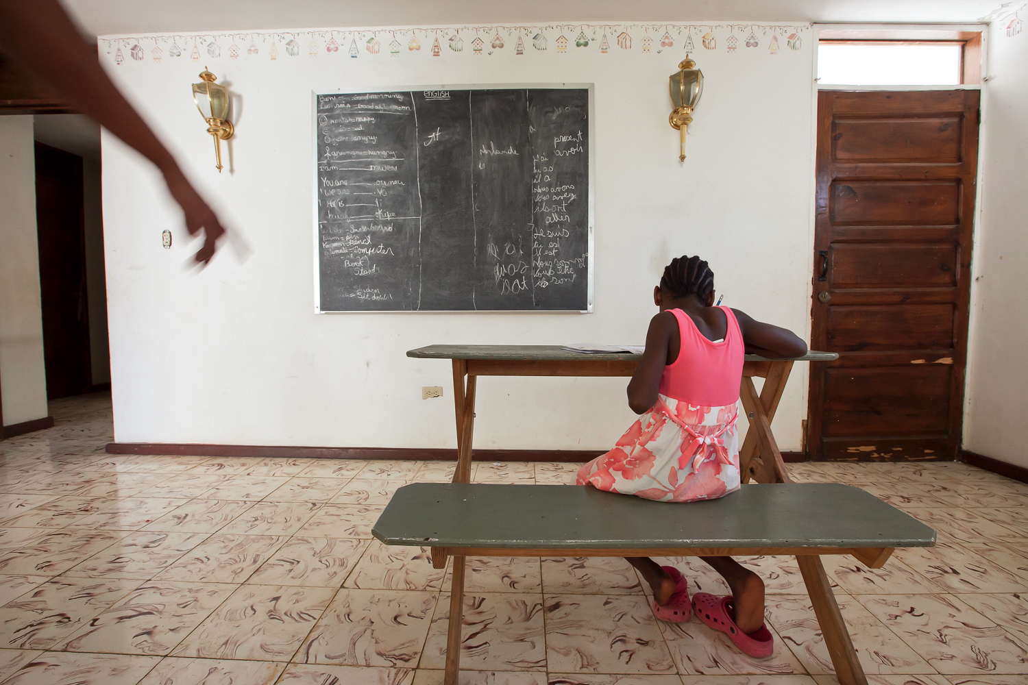 Children from a nearby orphanage also attend school regularly in Gramothe. On a day off from classes, a girl reviews lessons in the orphanage's common room.