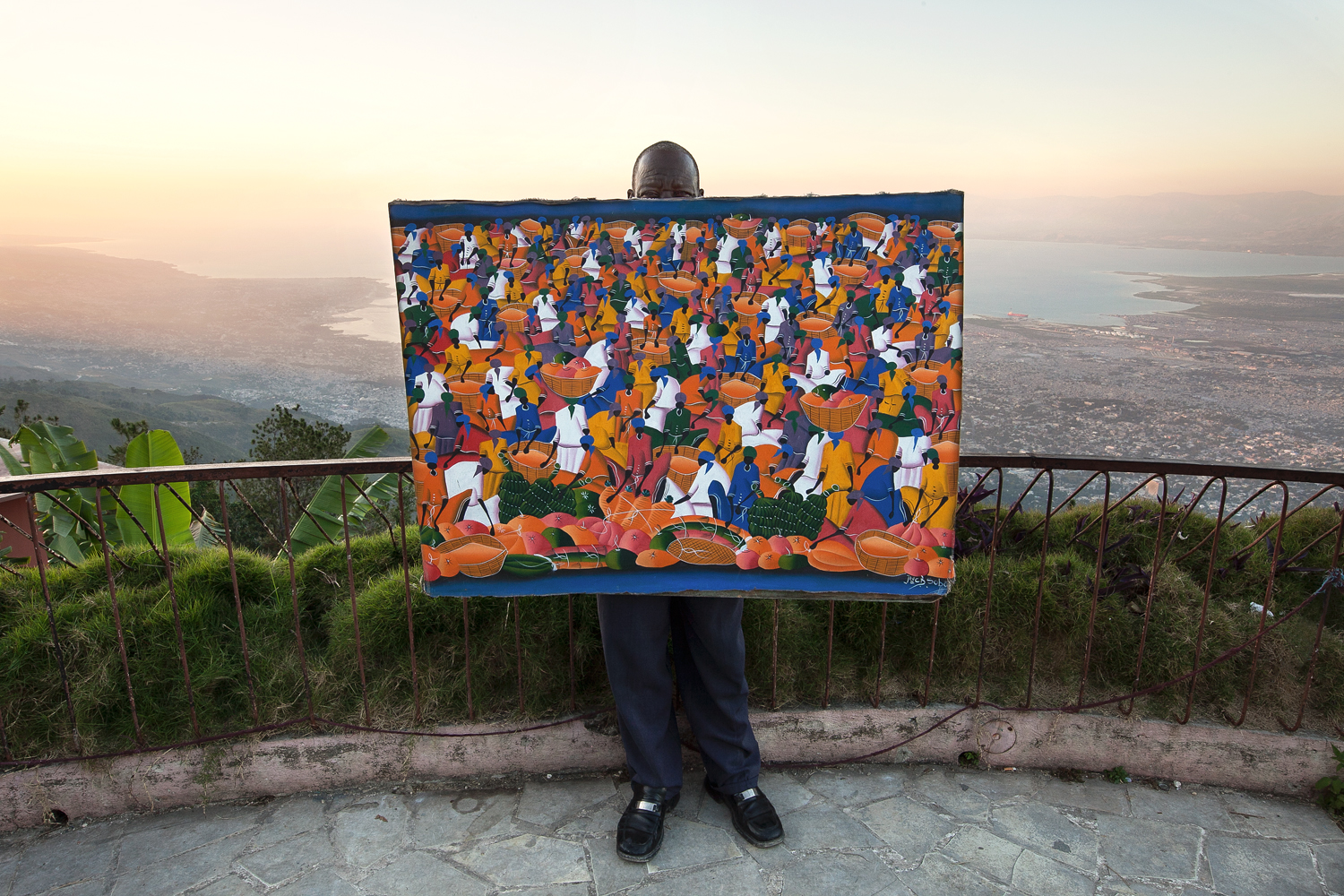 A local artist proudly holds his latest masterpiece depicting a traditional scene from the Haitian culture. He sells his work at a popular road-side lookout known for its view of Port-au-Prince.