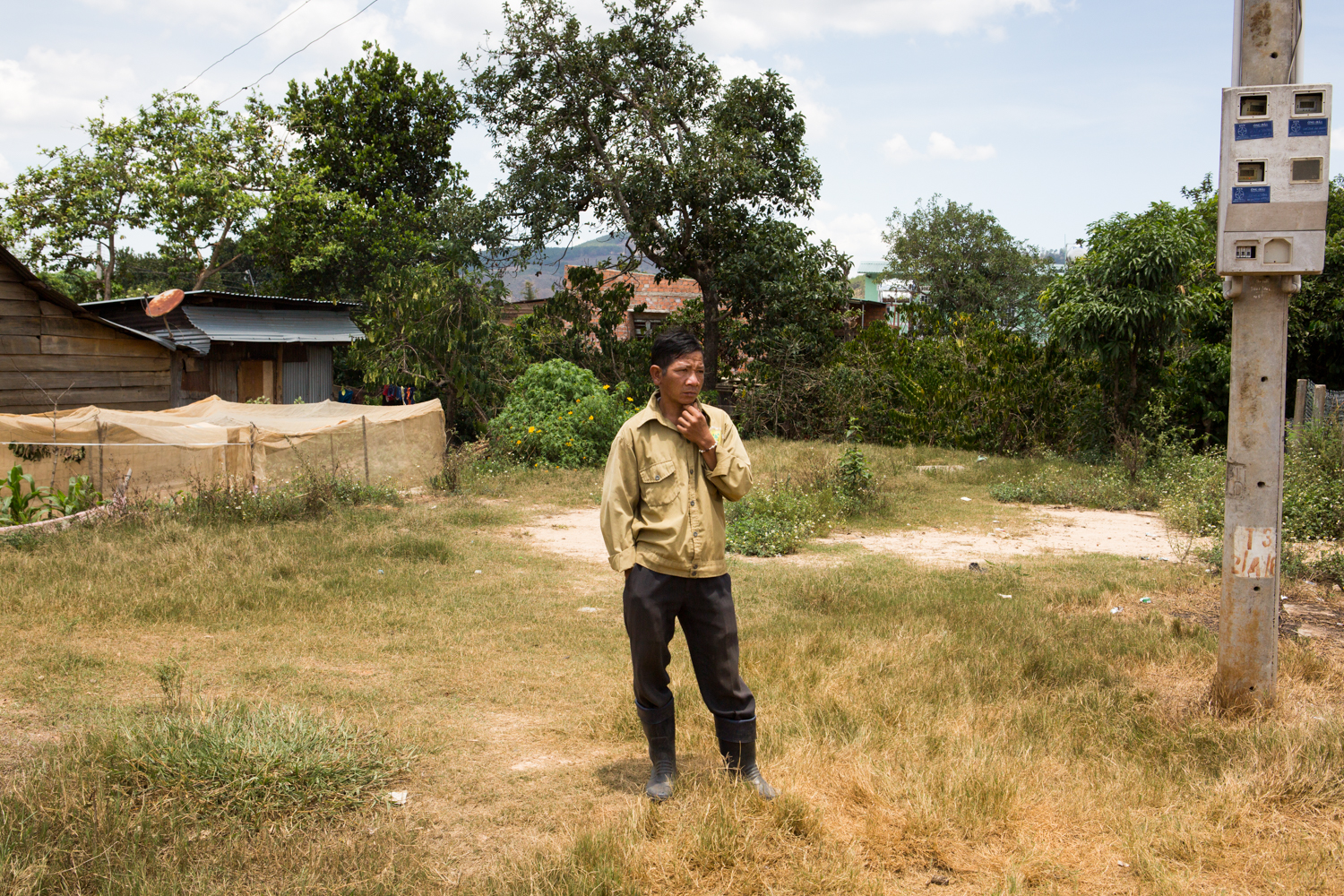 In a small village on the outskirts of Dalat, a man stands in a vacant housing lot.