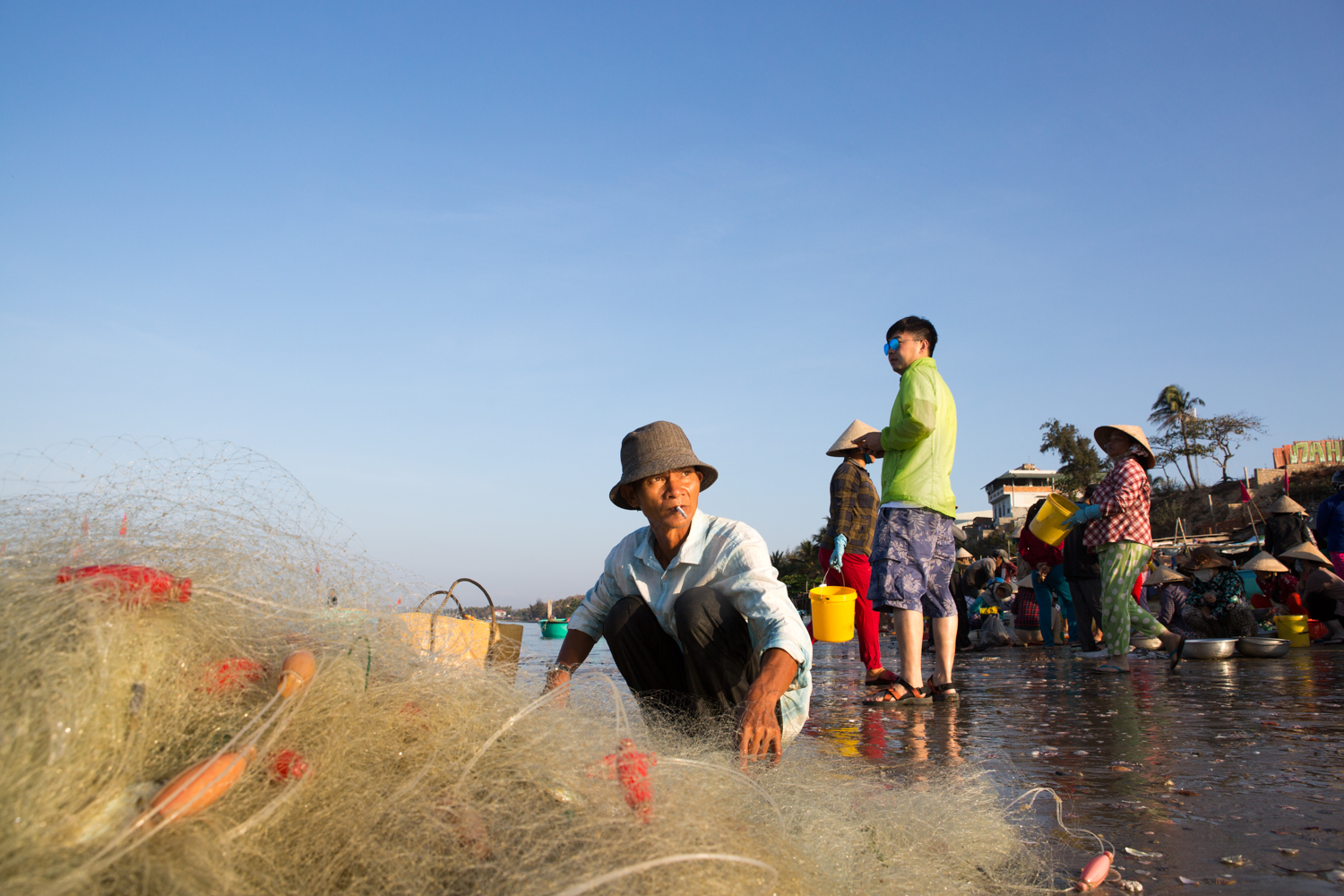 On the beach of Mui Ne, Vietnam, a man untangles his fishing net to collect his daily catch.
