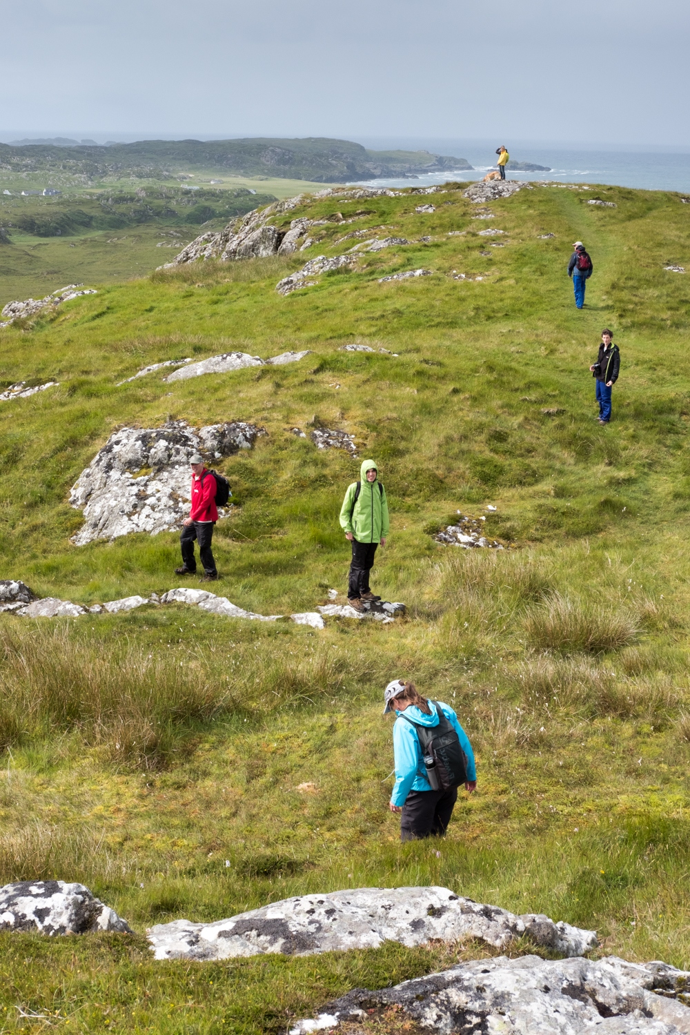 Several guests hike along a foot path on Dun I, a small hill overlooking the abbey on the island of Iona.