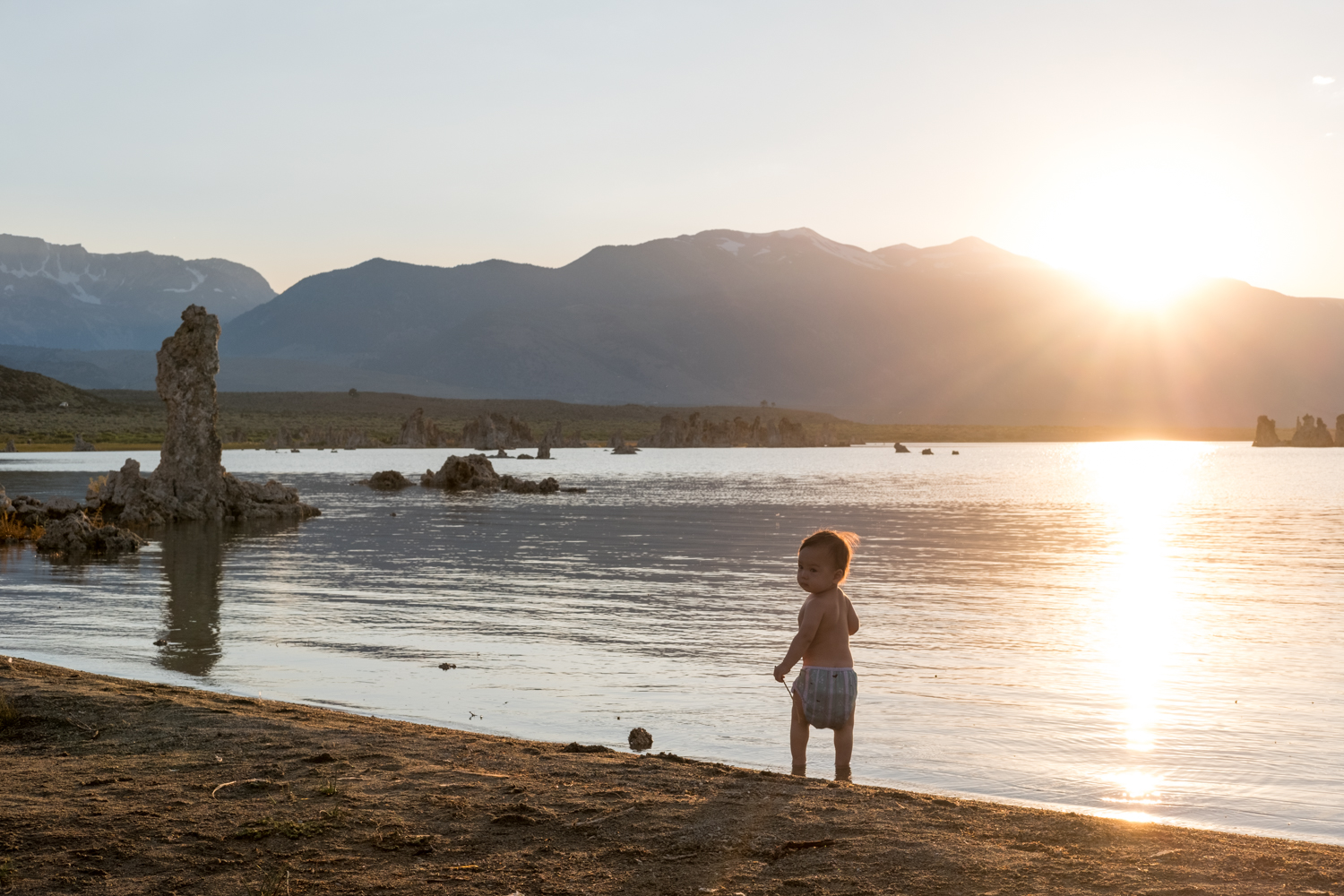 A young nature lover plays on the bank of Mono Lake at sunset.