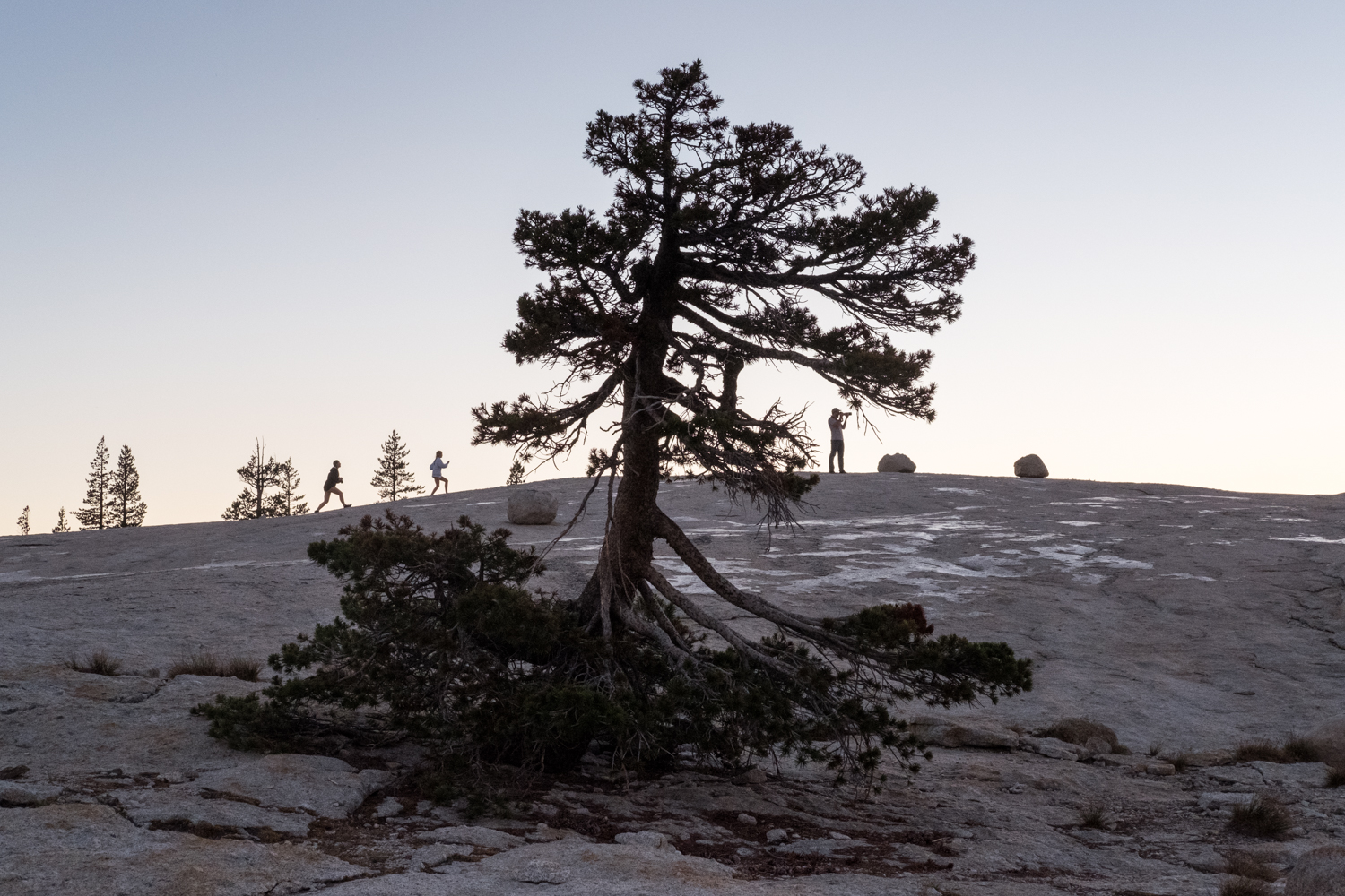 Photographers climb Pothole Dome, located on the west side of Tuolumne Meadows in Yosemite National Park.