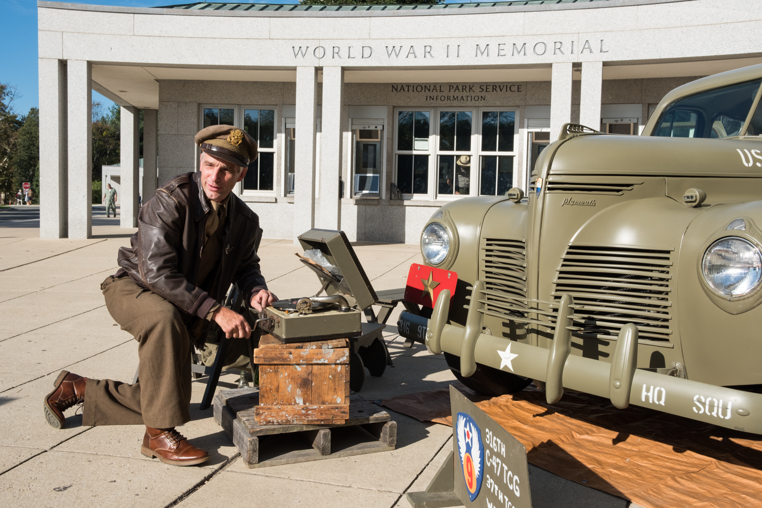 Chris Gabers, a war re-enactor with the Allied Airmen's Preservation Society, winds a record player near the World War II Memorial in Washington, D.C. during an Honor Flight event. Honor Flight is when veterans from around America visit the memorials on The National Mall.
