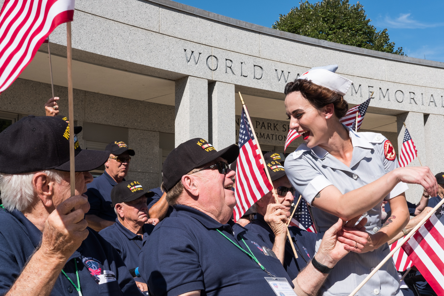 Hailey Shaw, a war re-enactor with the Allied Airmen's Preservation Society, greets veterans from the Austin, Texas Honor Flight Hub near the World War II Memorial in Washington, D.C. during an Honor Flight event. Honor Flight is when veterans from around America visit the memorials on The National Mall. The Allied Airmen's Preservation Society is a group of volunteers who gather during events to honor, preserve and remember veterans.