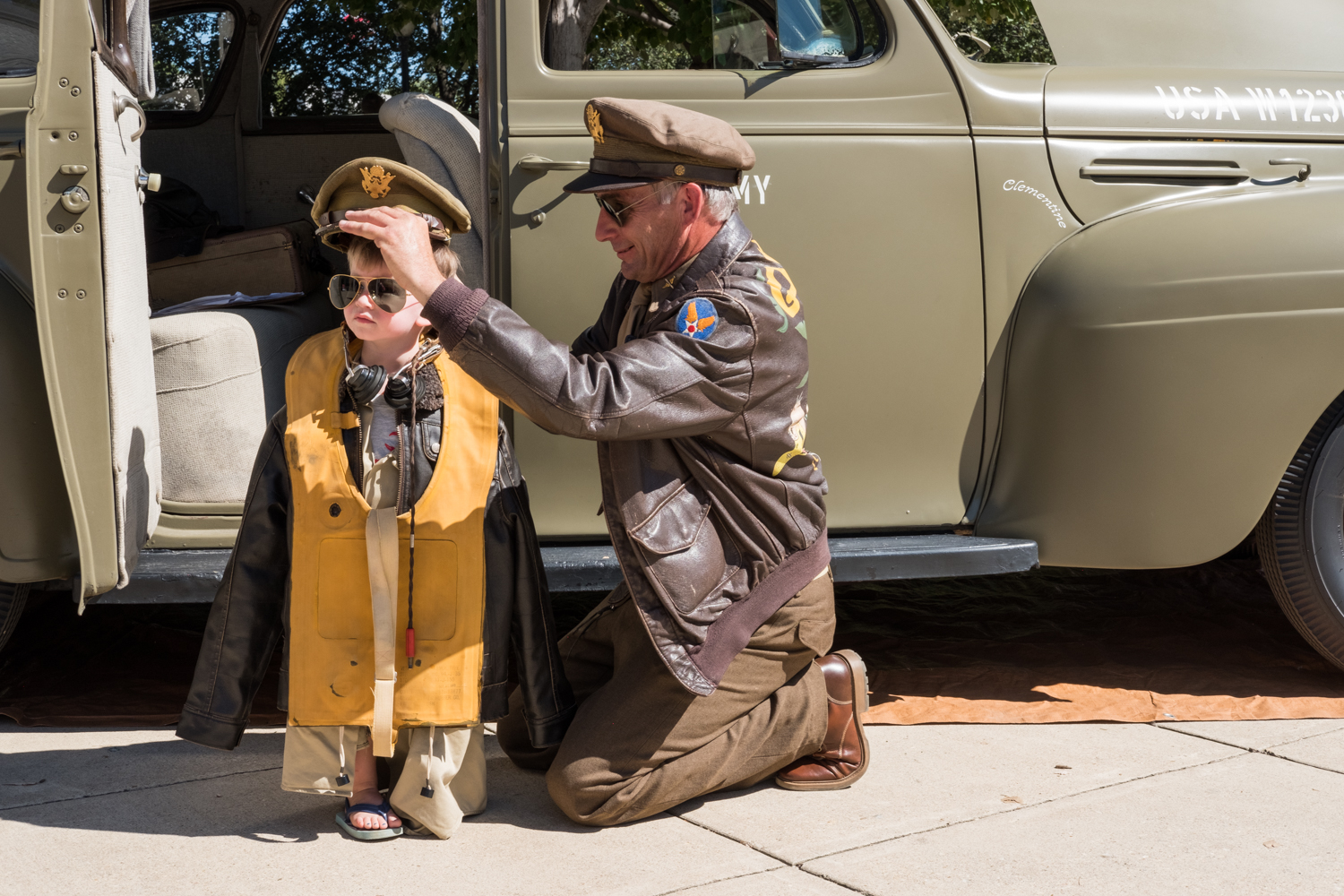 """Chris Gabers, a war re-enactor with the Allied Airmen's Preservation Society, dresses Kenneth Blasi in Army attire near the World War II Memorial in Washington, D.C. during an Honor Flight event. Honor Flight is when veterans from around America visit the memorials on The National Mall. Kenneth's grandfather, C Patrick McCourt, is a veteran and part of the U.S. Park Service """"Living History."""""""