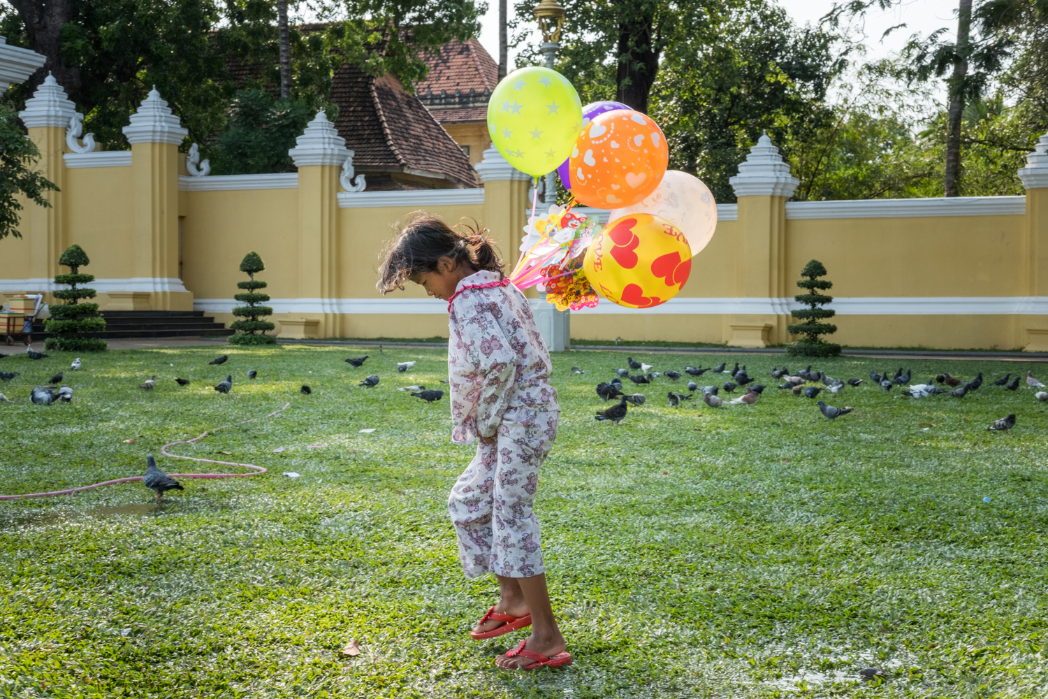 A young girl selling balloons walks through a wet and muddy field outside the palace in Phnom Penh, Cambodia.