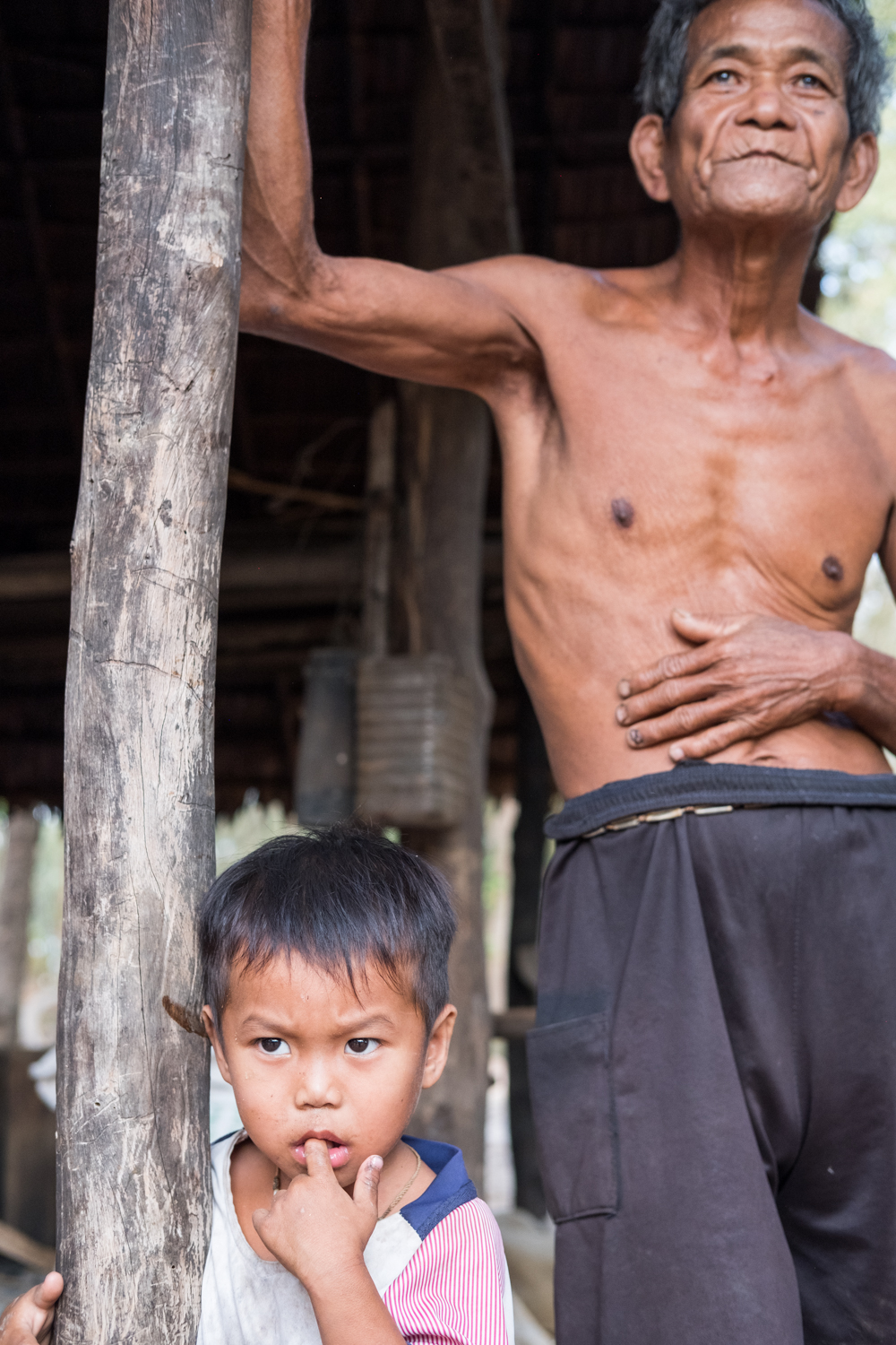 An uncle and his nephew pause next to a structure in Kampong Chhnang, Cambodia.