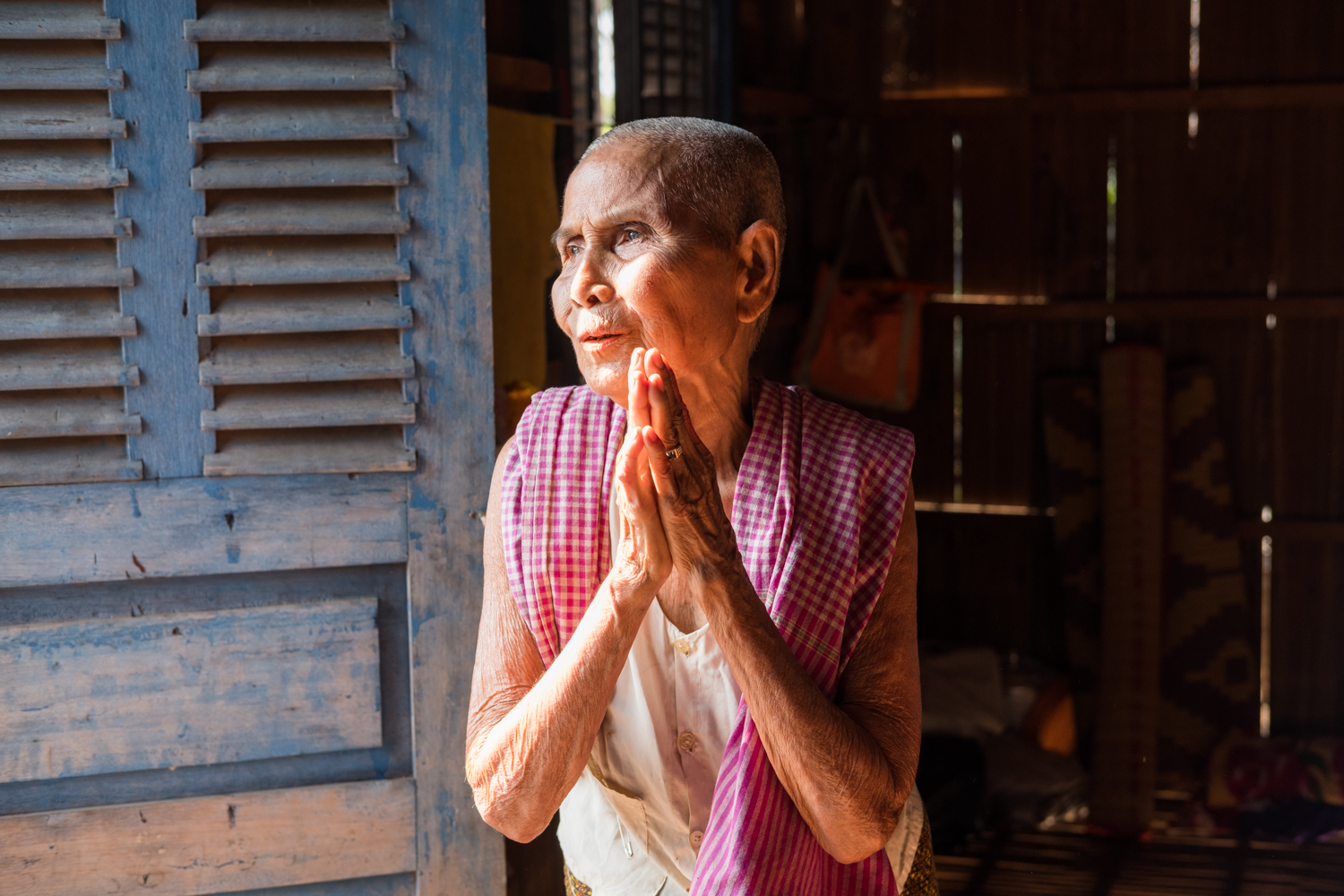 A local Cambodian woman in the village of Angkor Ban pauses for a moment of reflection in her home's doorway.