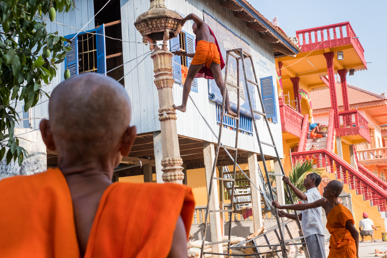 A group of monks perform construction activities outside their temple in Angkor Ban, Cambodia.