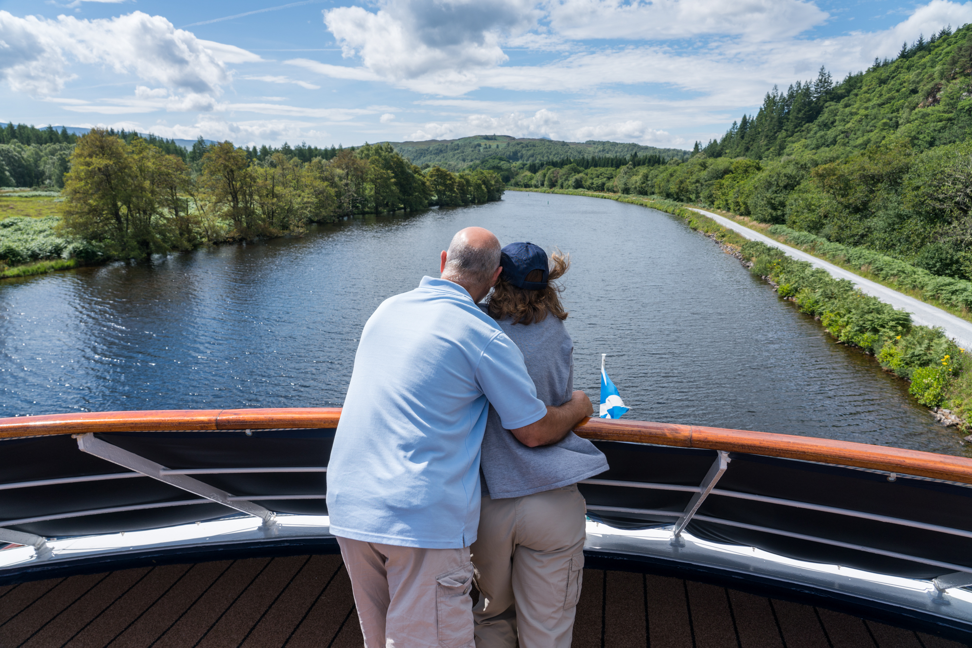 A couple shares a moment while enjoying the view and scenery along The Caledonian Canal from the bow of Lord of the Glens.