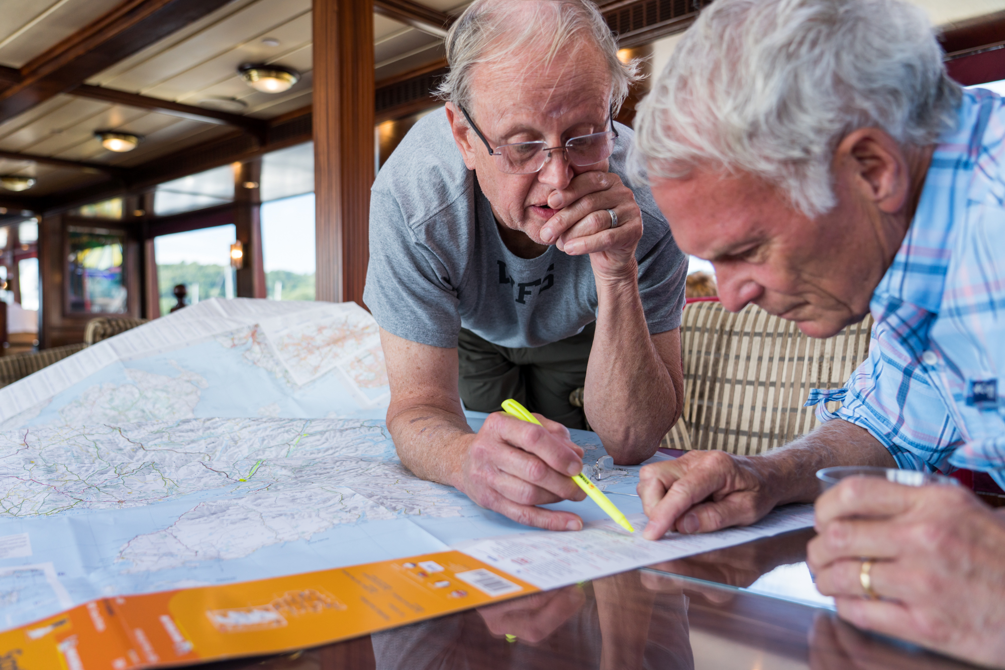 Two guests study the legend on a Scotland map while aboard Lord of the Glens.