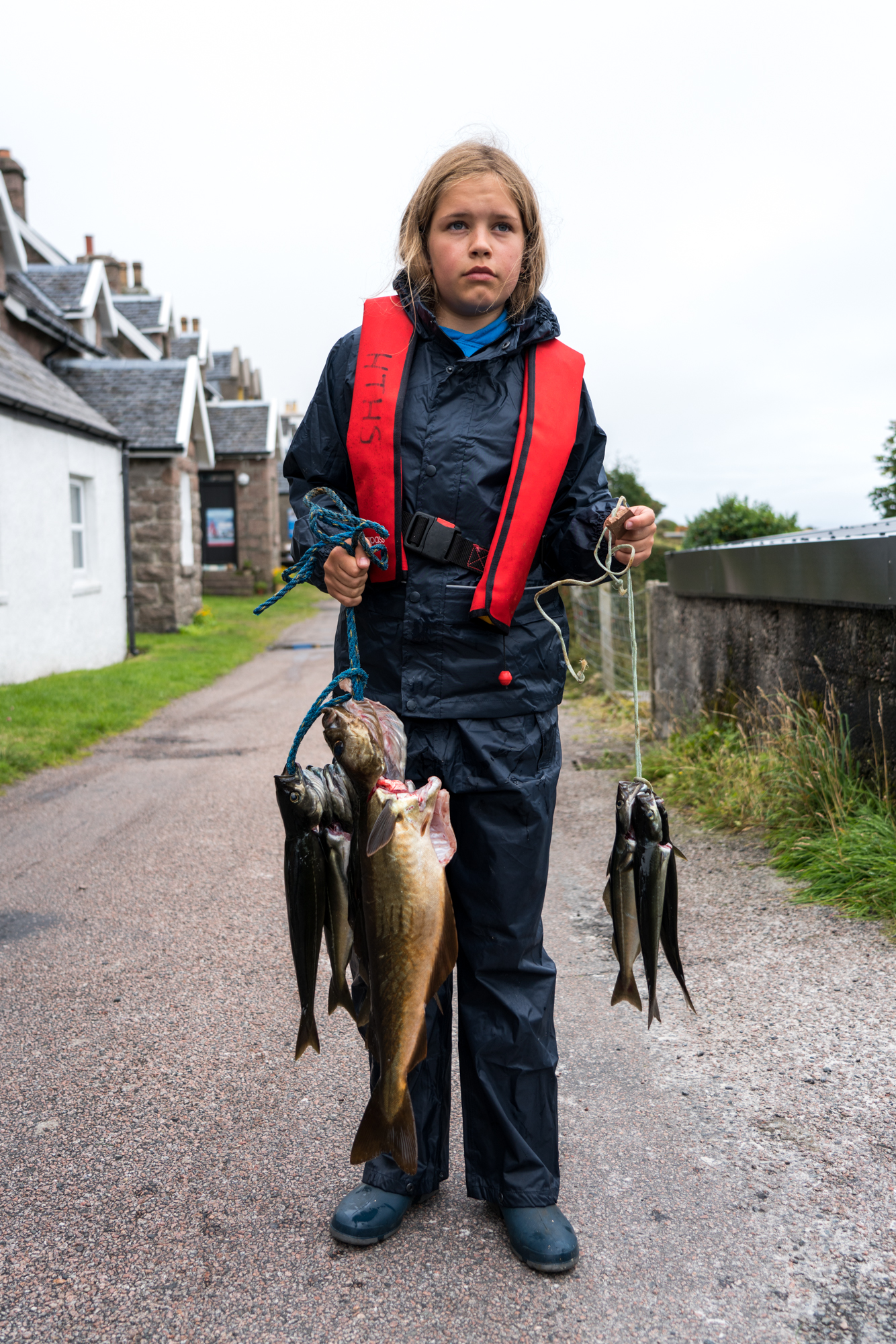 On Iona, Scotland, a young girl poses for a portrait while displaying her local daily catch.