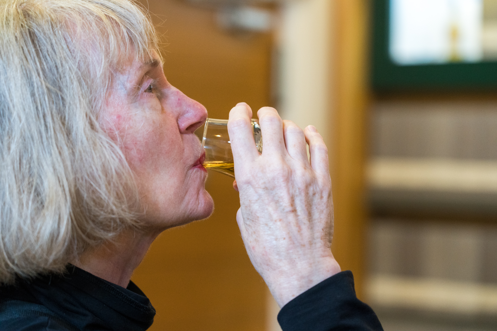 A woman samples Oban Whisky in the distillery tasting room.