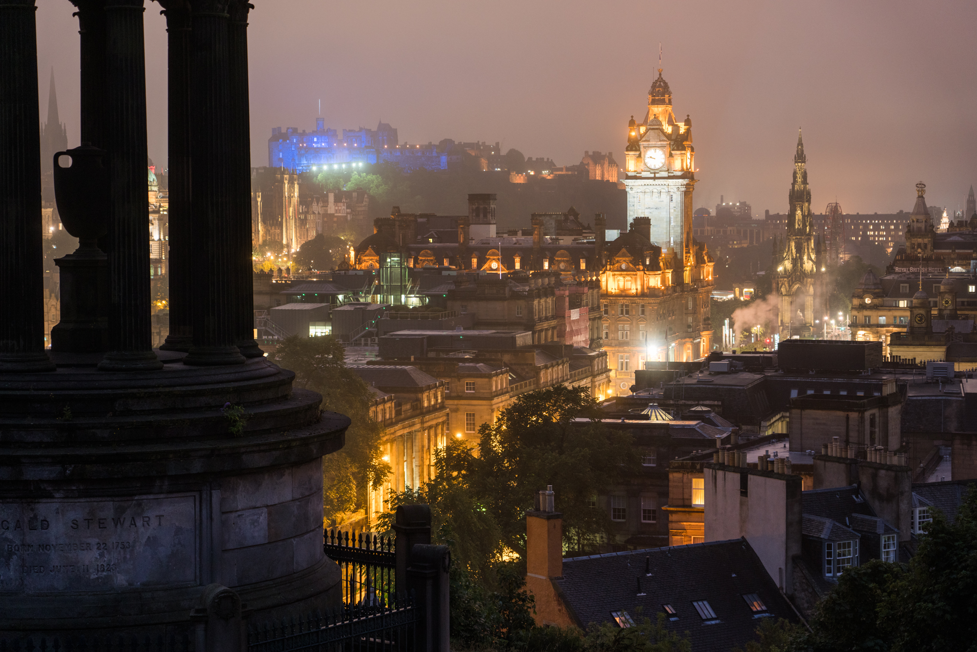 The Balmoral Hotel's tower and The Edinburgh Castle are illuminated at dusk as seen from Calton Hill.