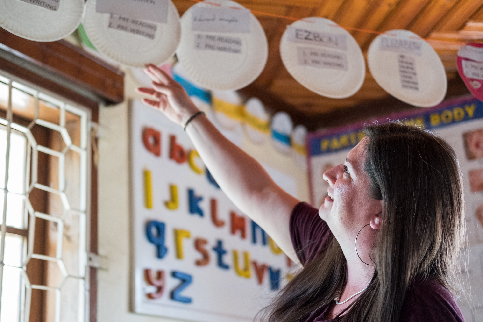 Holly looks at plates hanging in a classroom at Child Support Tanzania. Each plate is assigned to one student and has a list of his/her current learning activities.