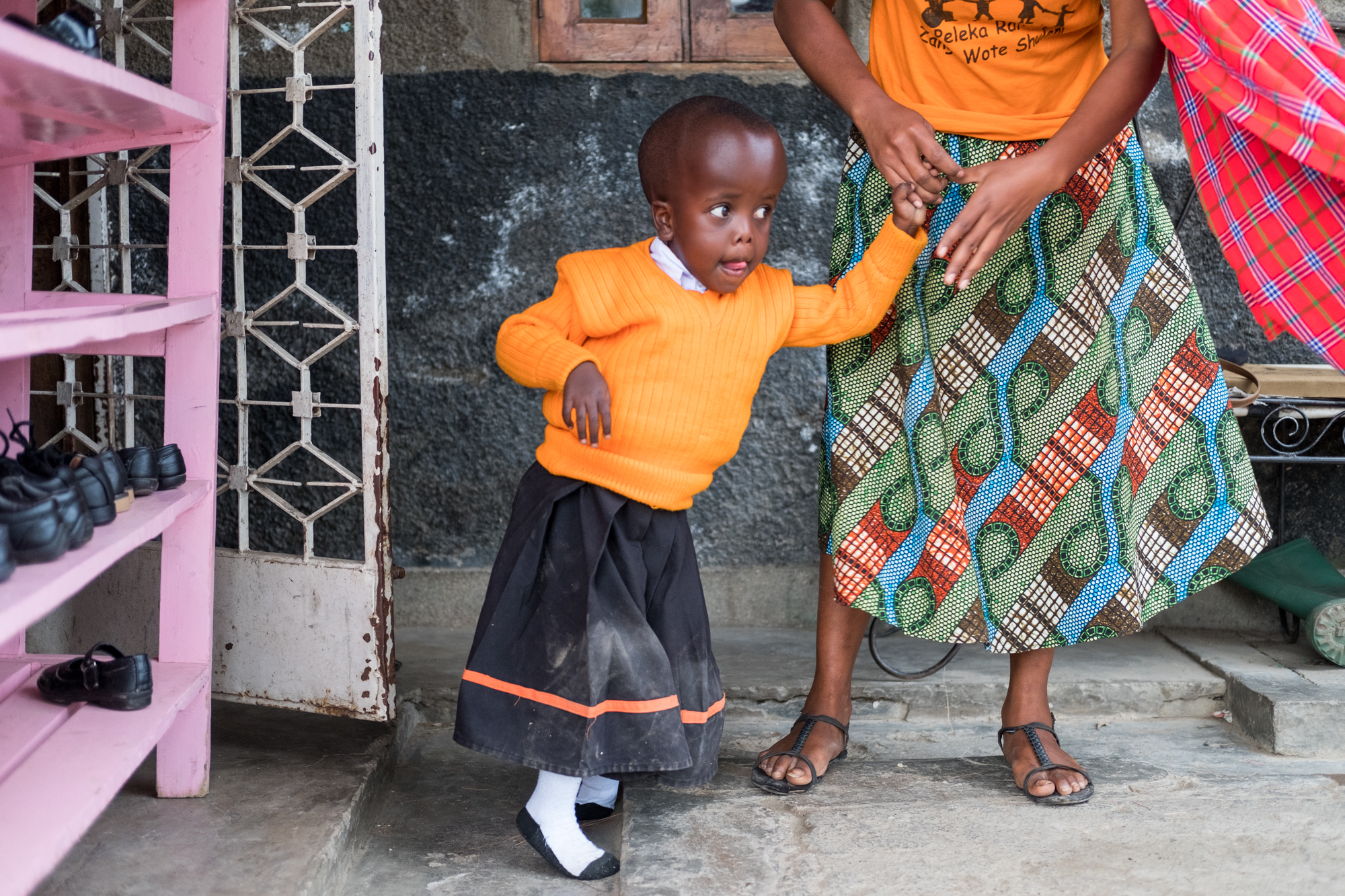A teacher helps a student (Felistar Sabbi Mwangolela) stand up and walk at Child Support Tanzania, a non-governmental organization located in Mbeya, Tanzania, that educates disabled children.