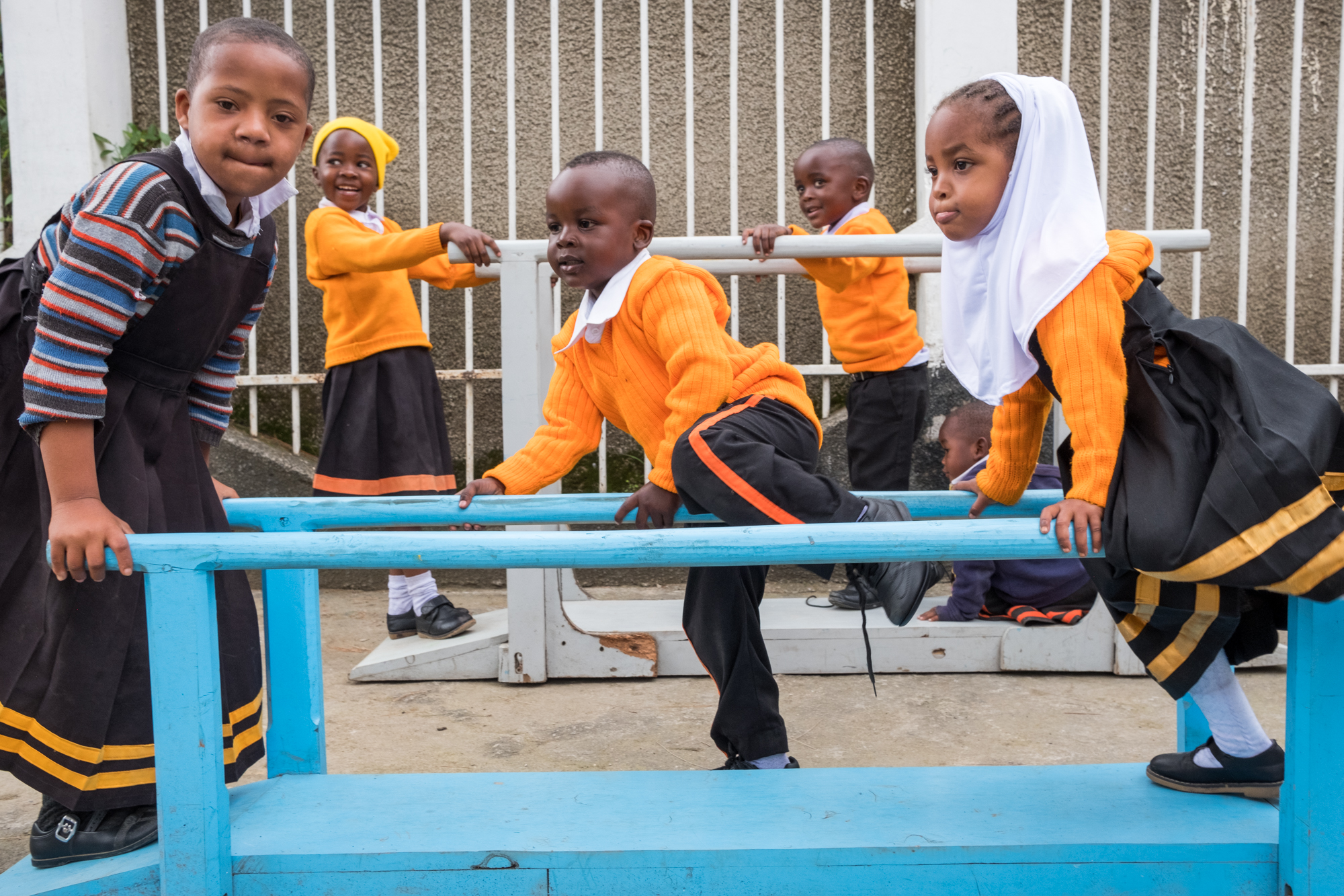 Students at Child Support Tanzania interact and play on assisted walking equipment.